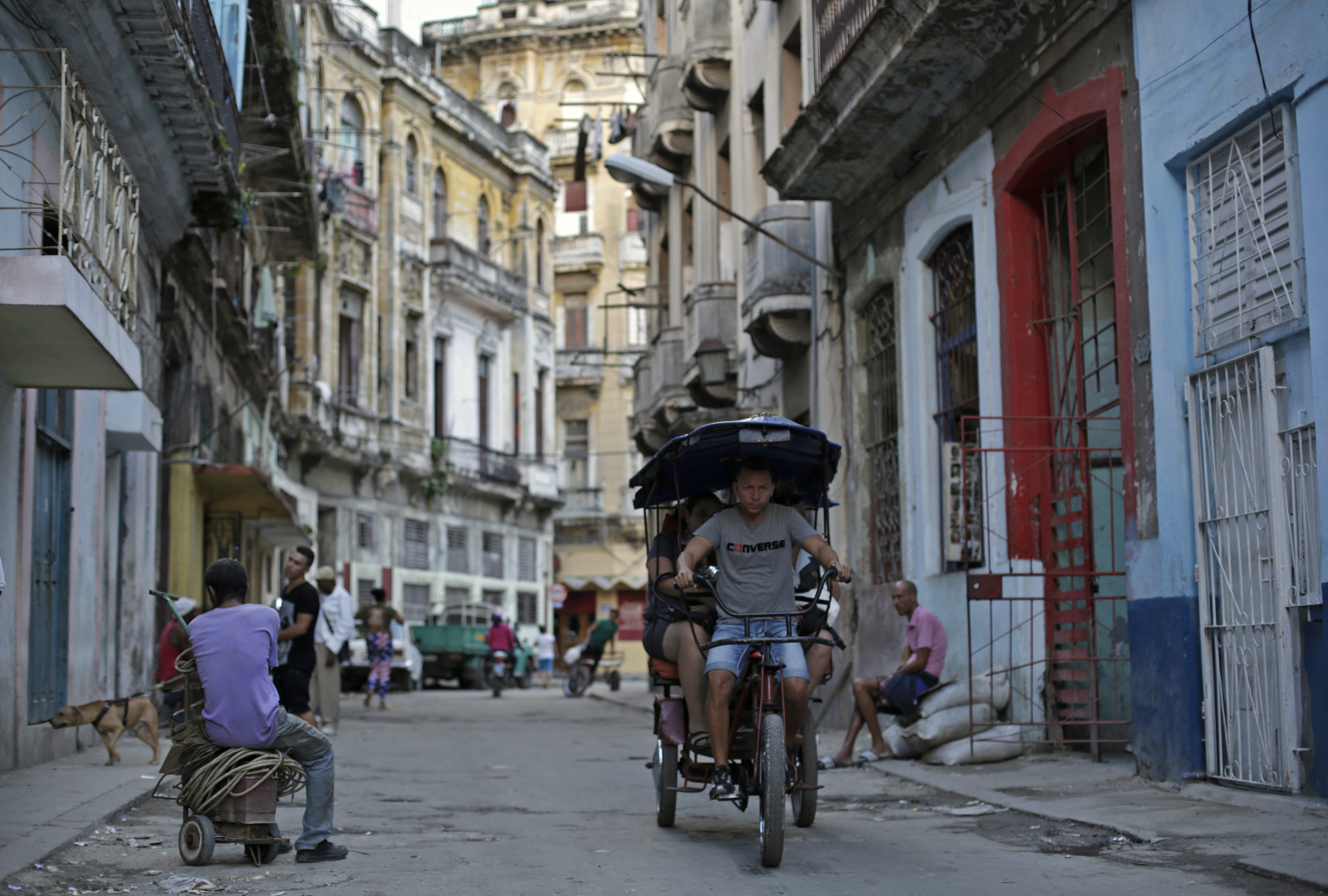 A man fetches passengers on his tricycle taxi in Havana