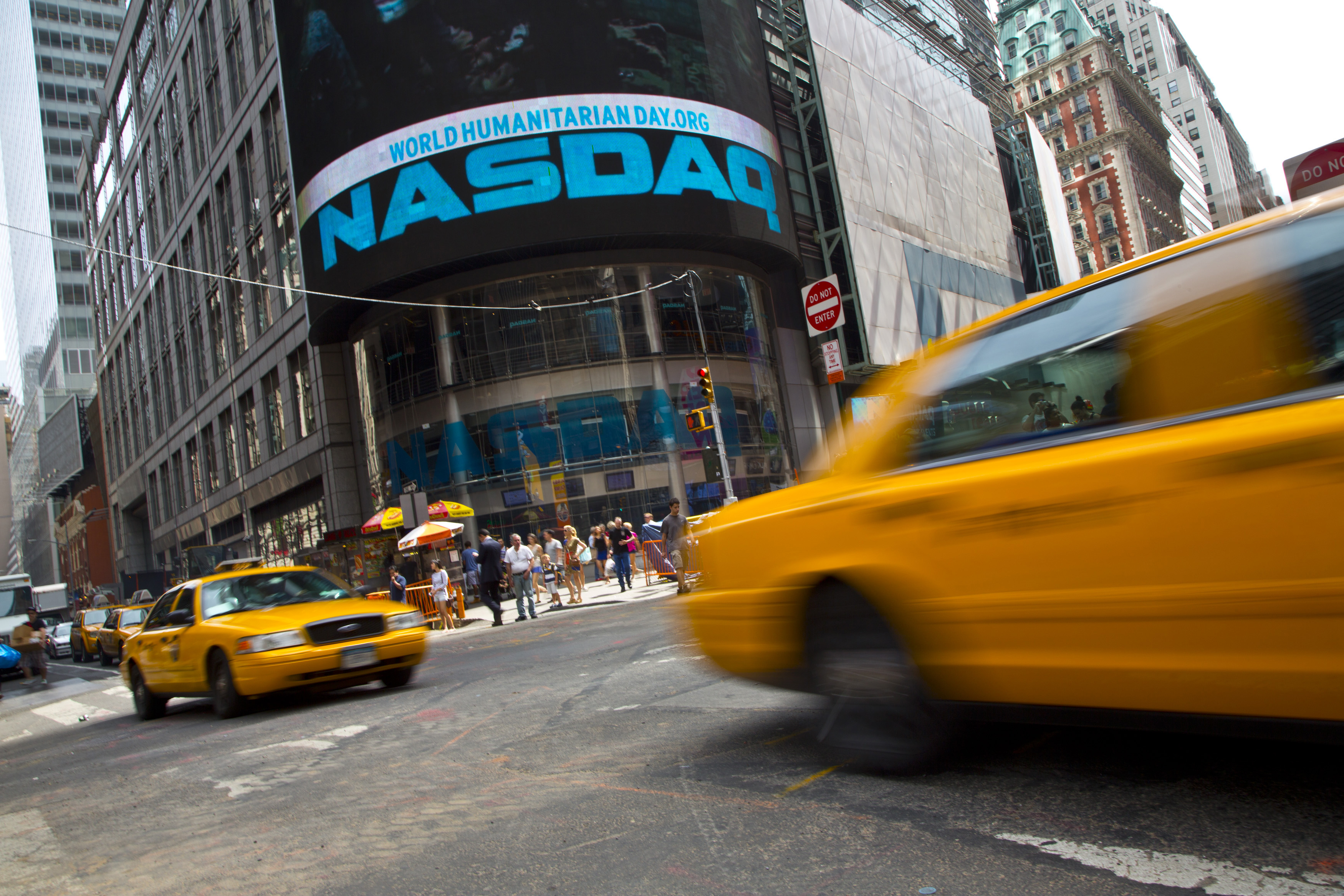 Taxi cabs drive  past the Nasdaq MarketSite in New York's Times Square