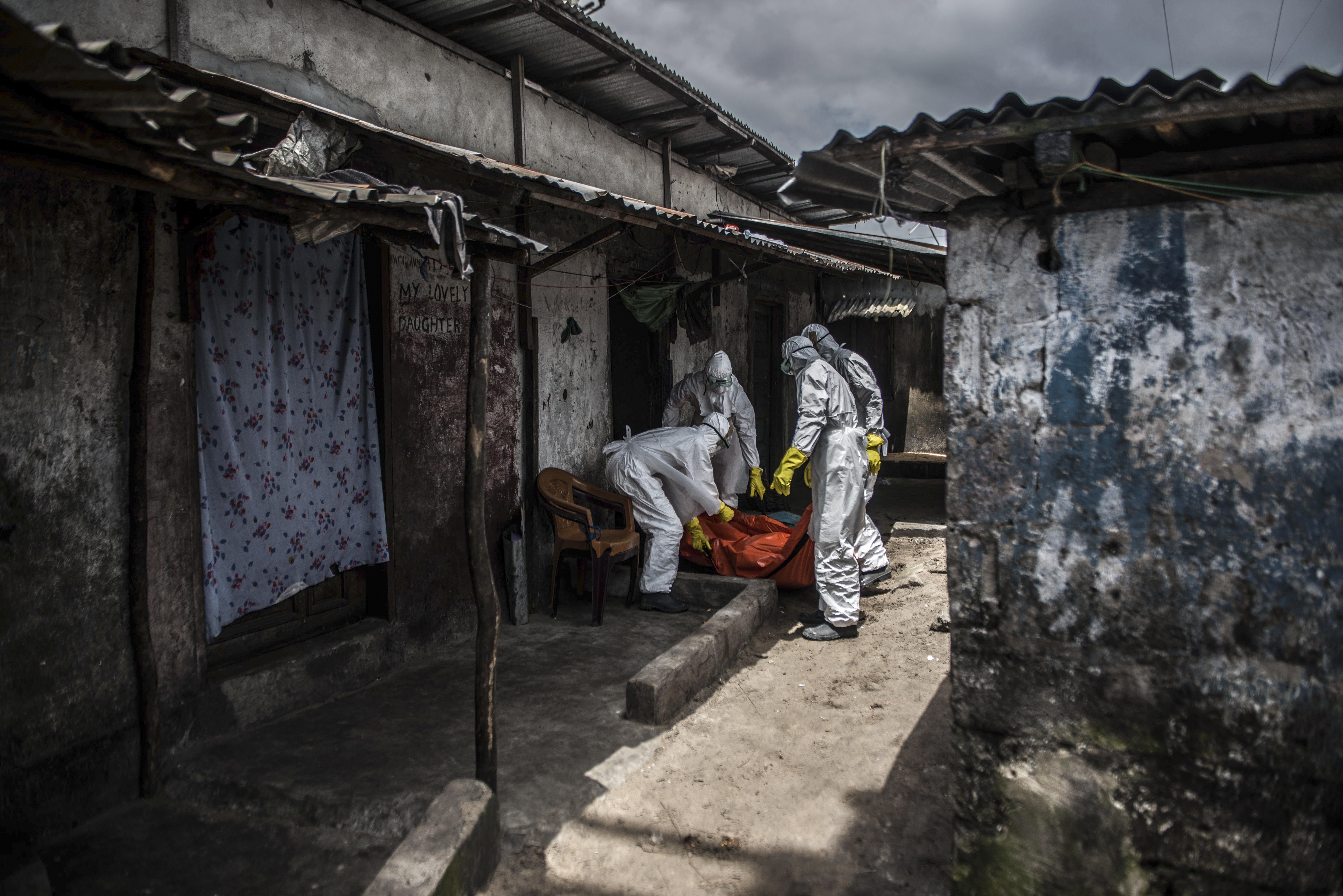 MONROVIA, LIBERIA - OCTOBER 15: Red Cross members carry dead body of Mambodou Aliyu (35) died due to the Ebola virus,, in Monrovia, Liberia on 15 October, 2014. (Photo by Mohammed Elshamy/Anadolu Agency/Getty Images)