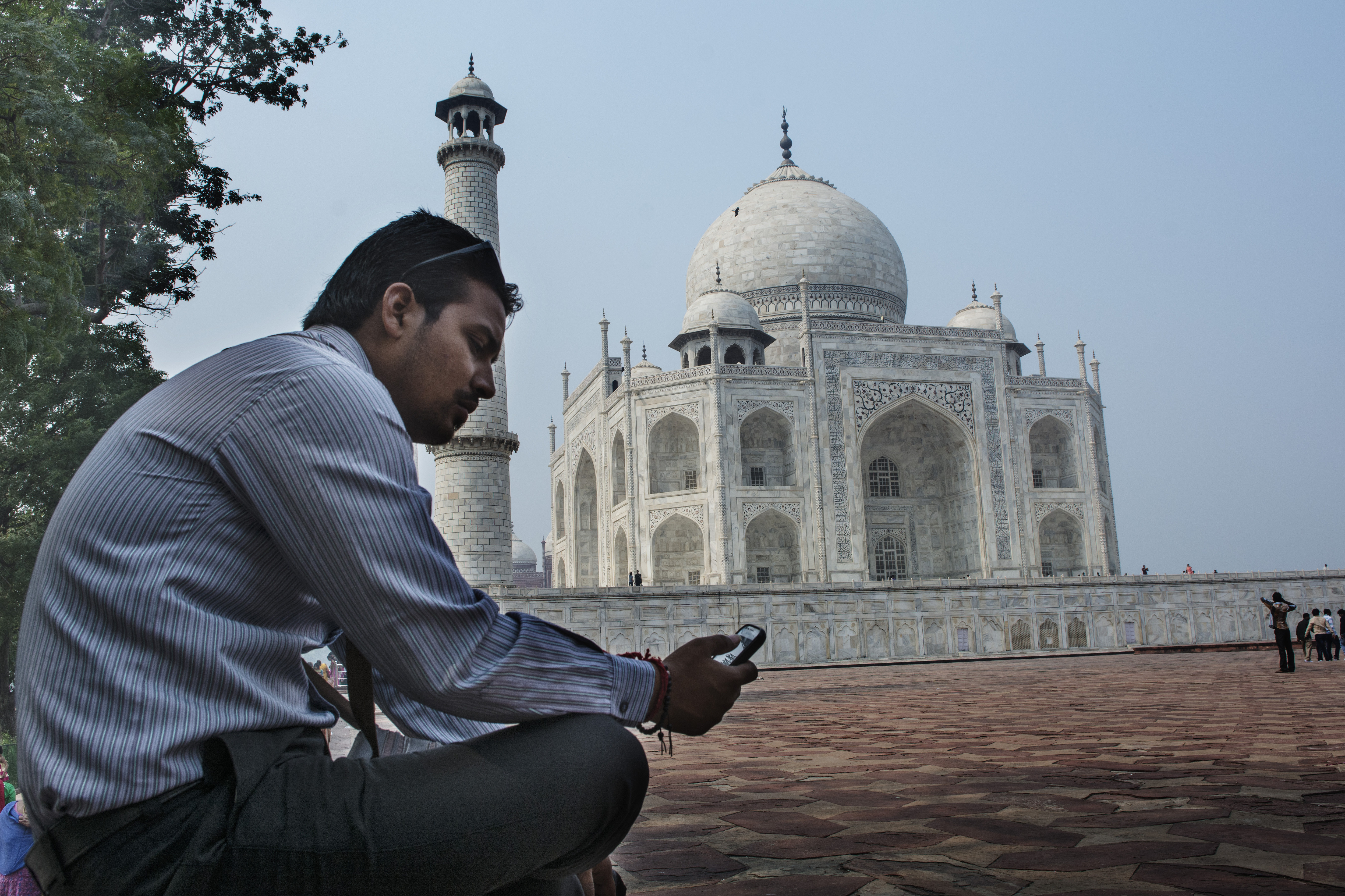 A man checks his cell phone in front of the Taj Mahal. The