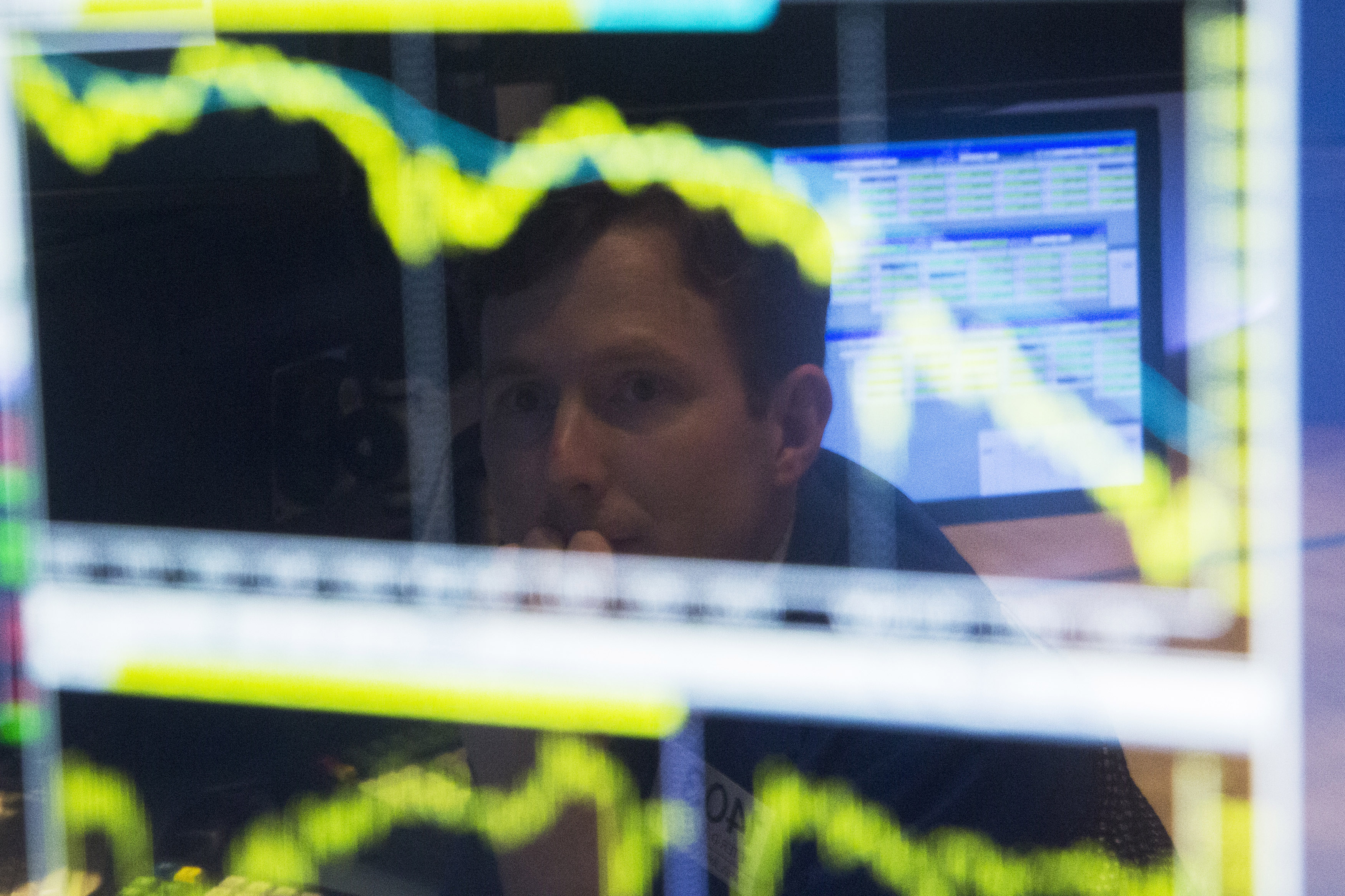 Trader watches the screen at his terminal on the floor of the New York Stock Exchange in New York