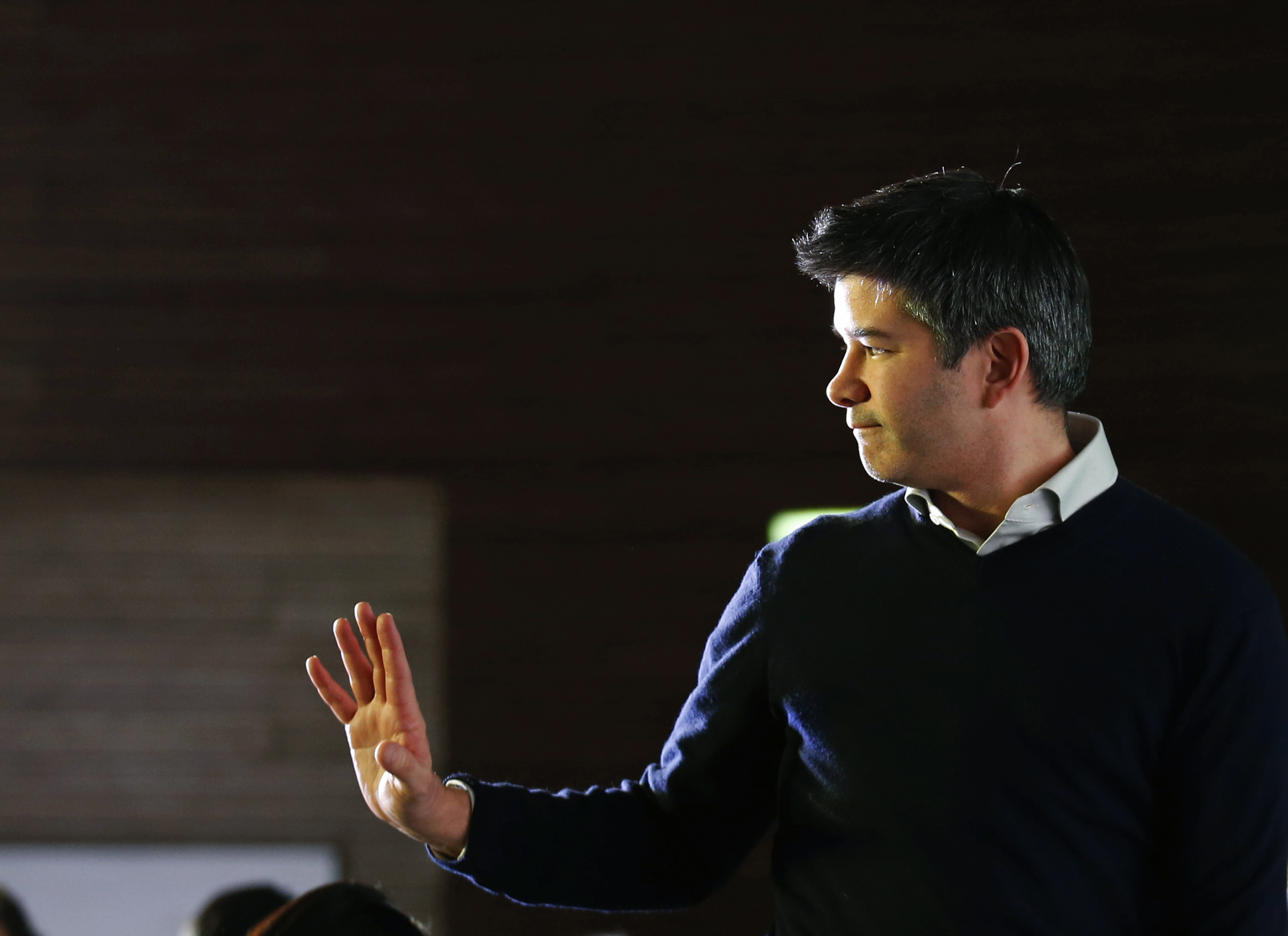 Uber CEO Kalanick acknowledges attendees during the Baidu and Uber strategic cooperation and investment signing ceremony in Beijing