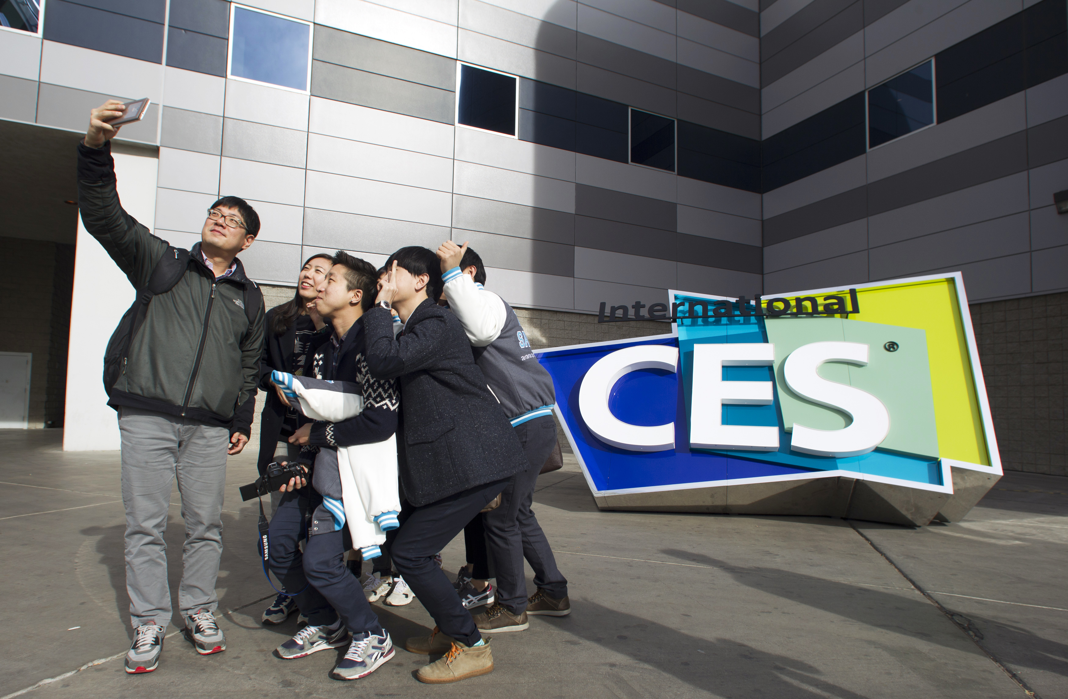 South Korean university students take a selfie in front of an International CES sign at the Las Vegas Convention Center in Las Vegas