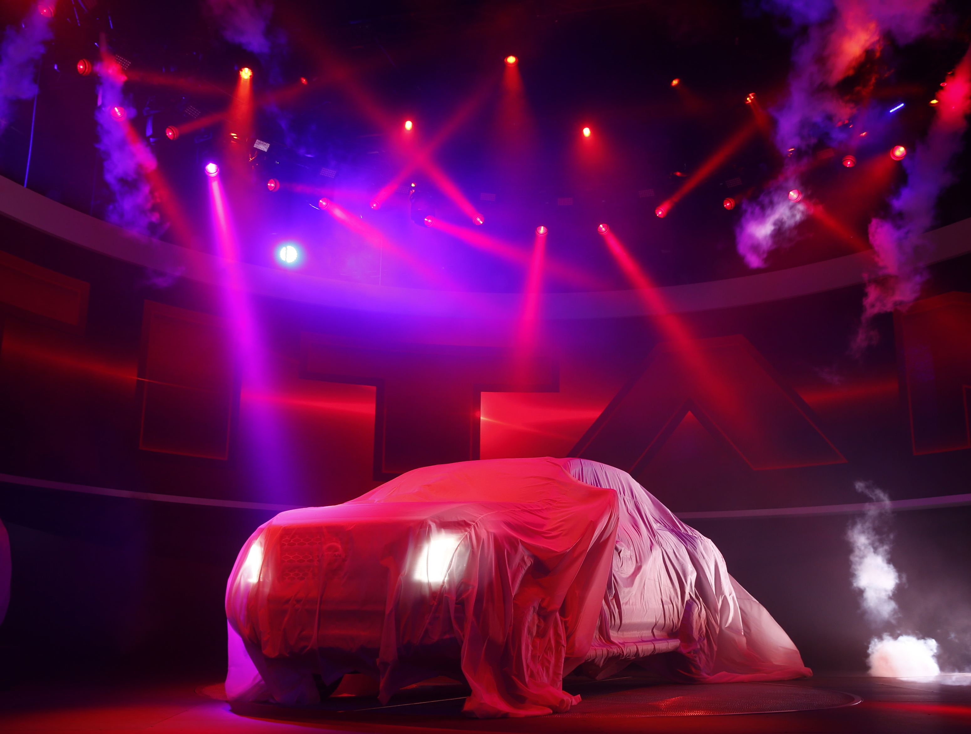 The 2016 Nissan Titan pickup truck is shown under a cover during its unveiling at the first press preview day of the North American International Auto Show in Detroit