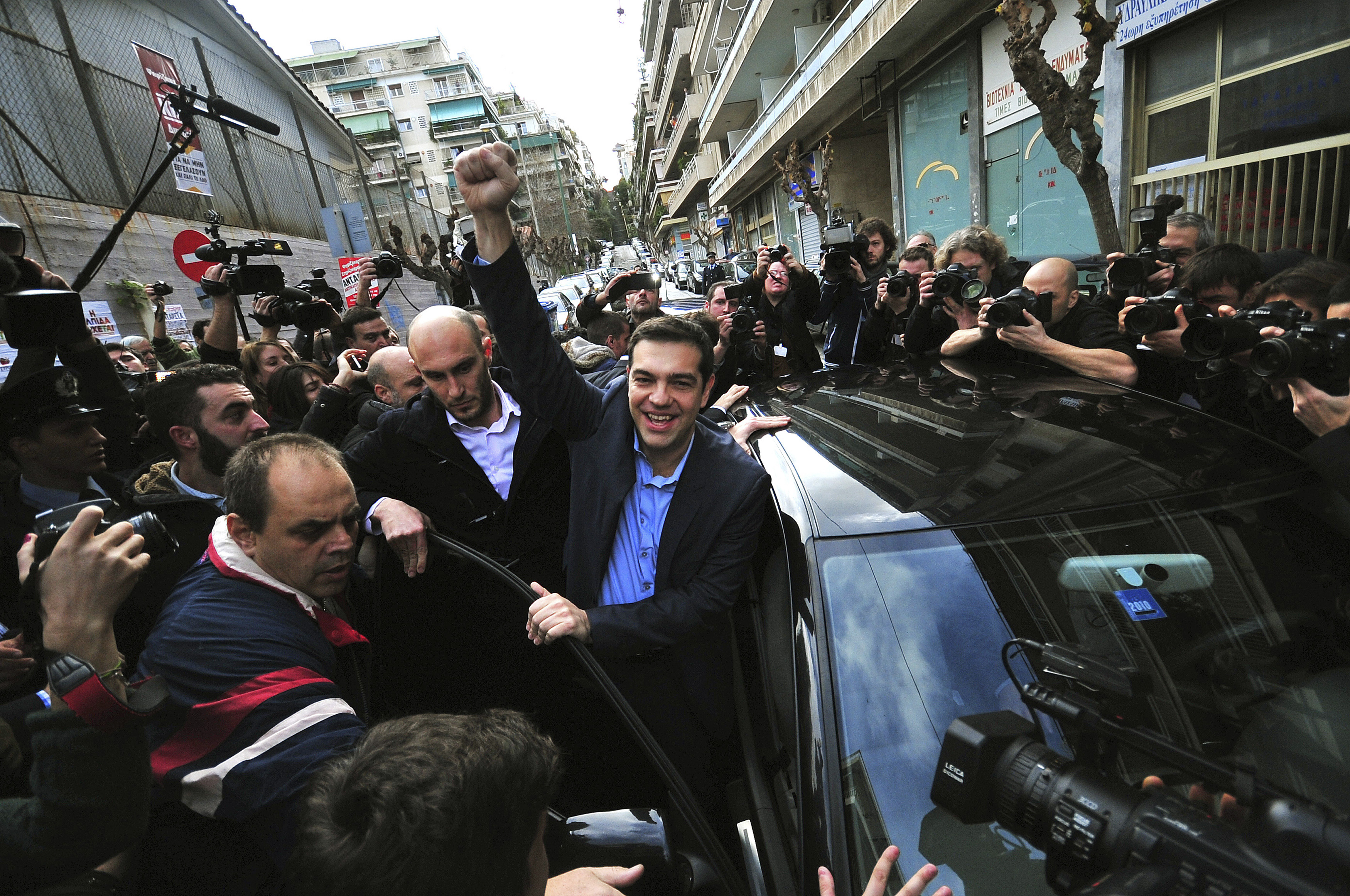 Opposition leader and head of radical leftist Syriza party Alexis Tsipras raises his fist as he leaves a polling station where he voted in Athens