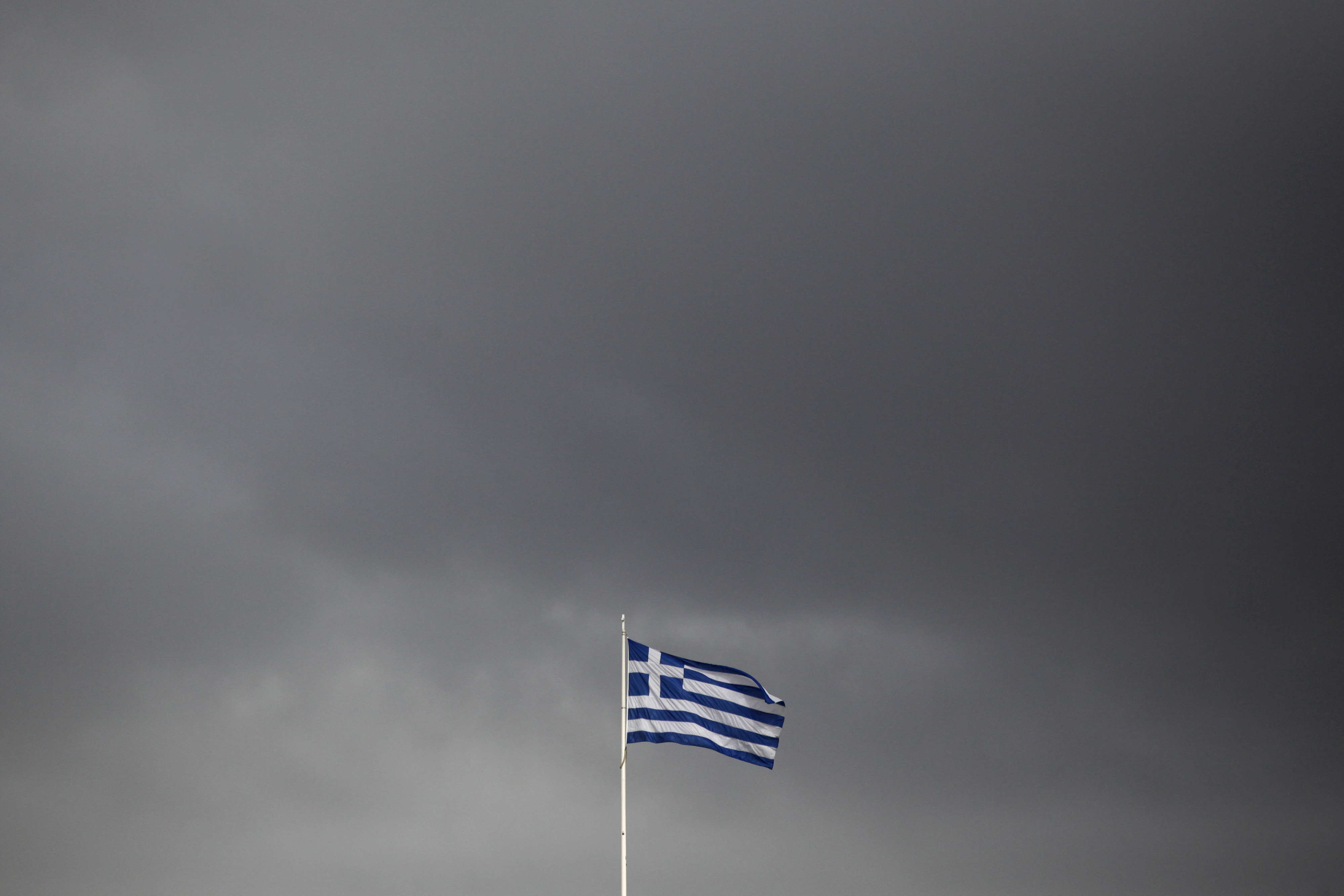 A European Union (EU) flag flies above the Greek parliament in Athens, Greece, on Tuesday, Feb. 24, 2015. Greece moved closer to winning an extension of financial aid after the head of the group of euro-region finance ministers said creditors were favorable toward the government's package of new economic measures. Photographer: Kostas Tsironis/Bloomberg