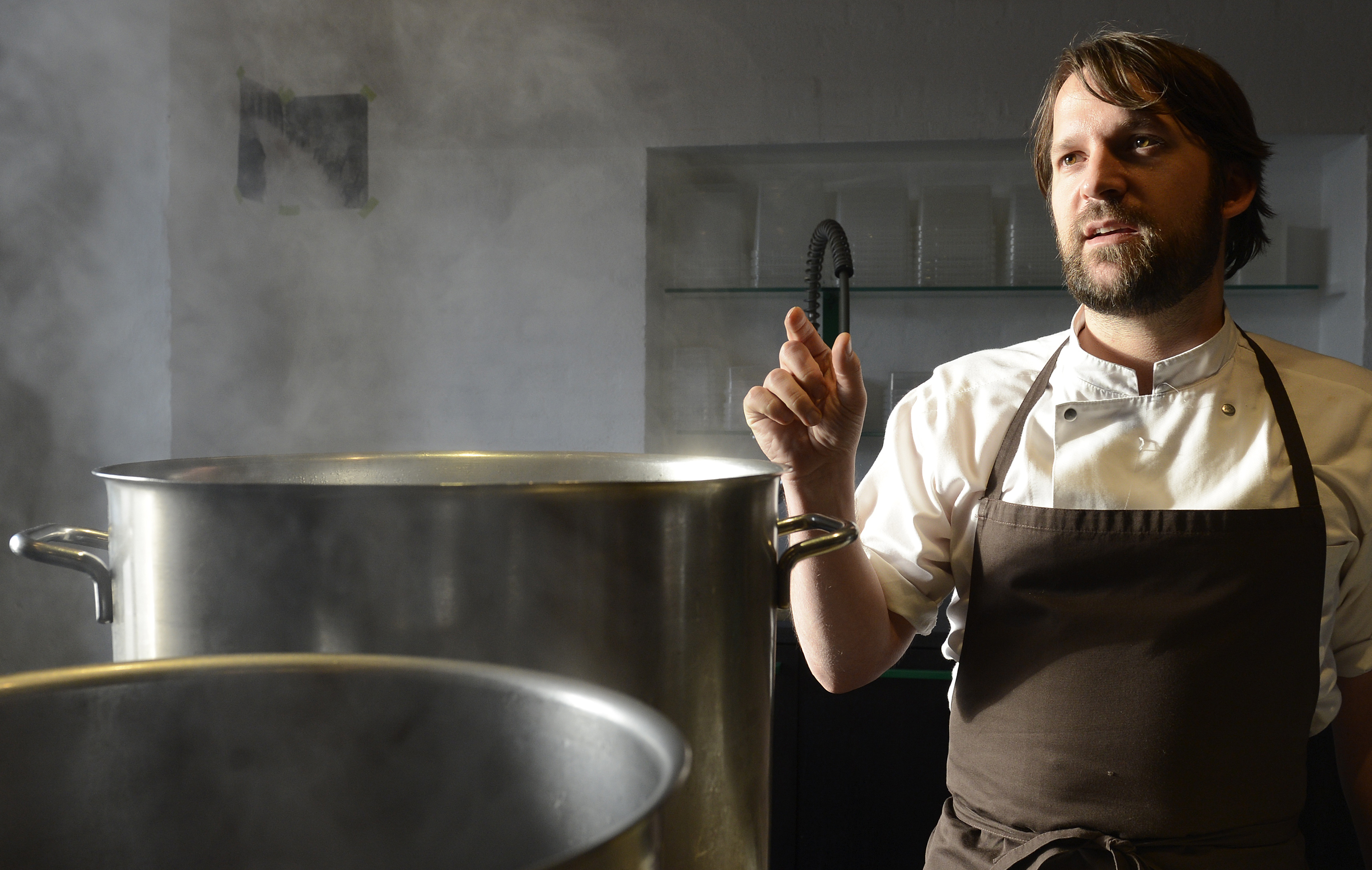 Redzepi, chef and co-owner of the restaurant Noma, talks with his employees in a test kitchen in his restaurant in Copenhagen