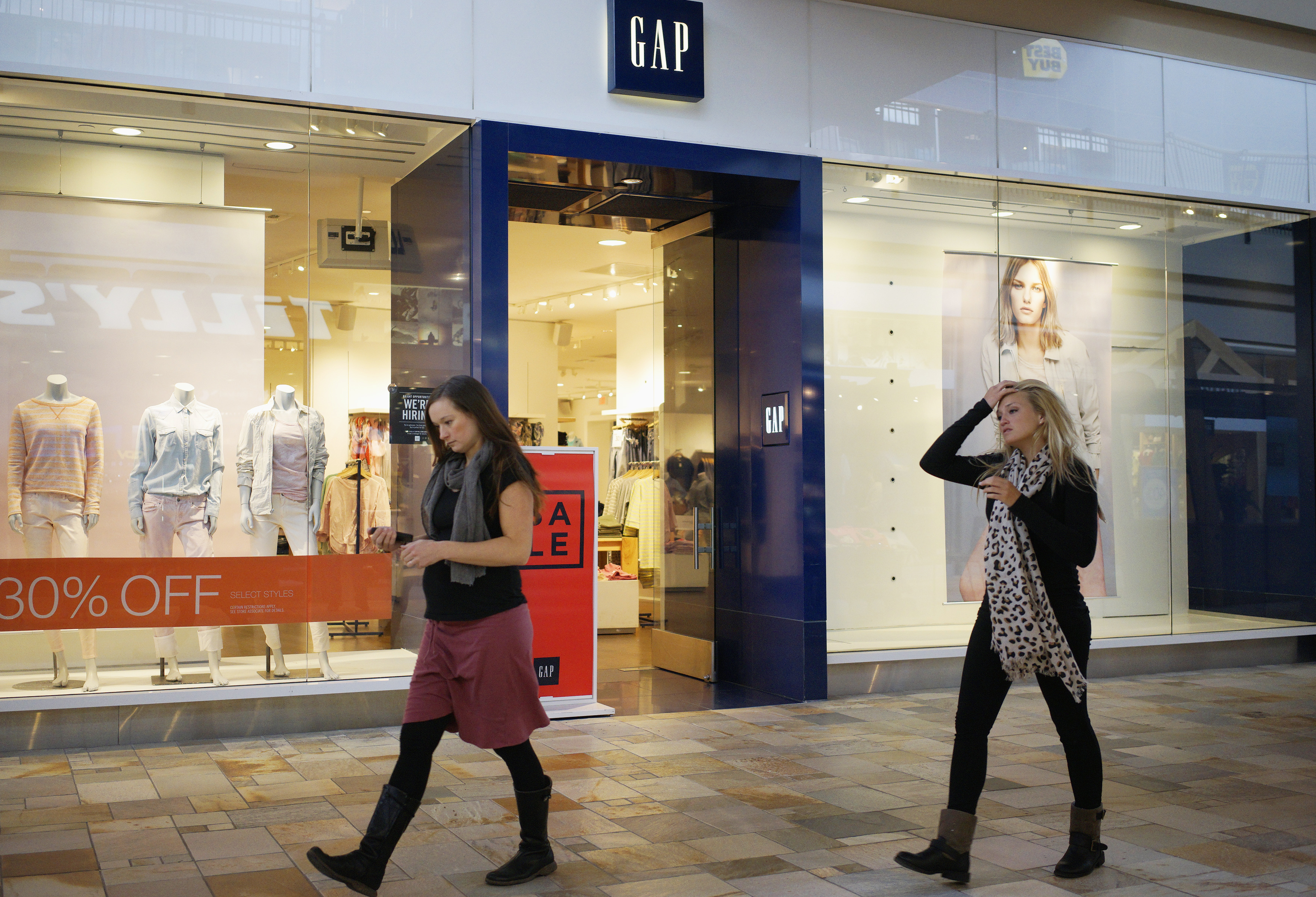 Passers-by walk next to a Gap store in Broomfield, Colorado