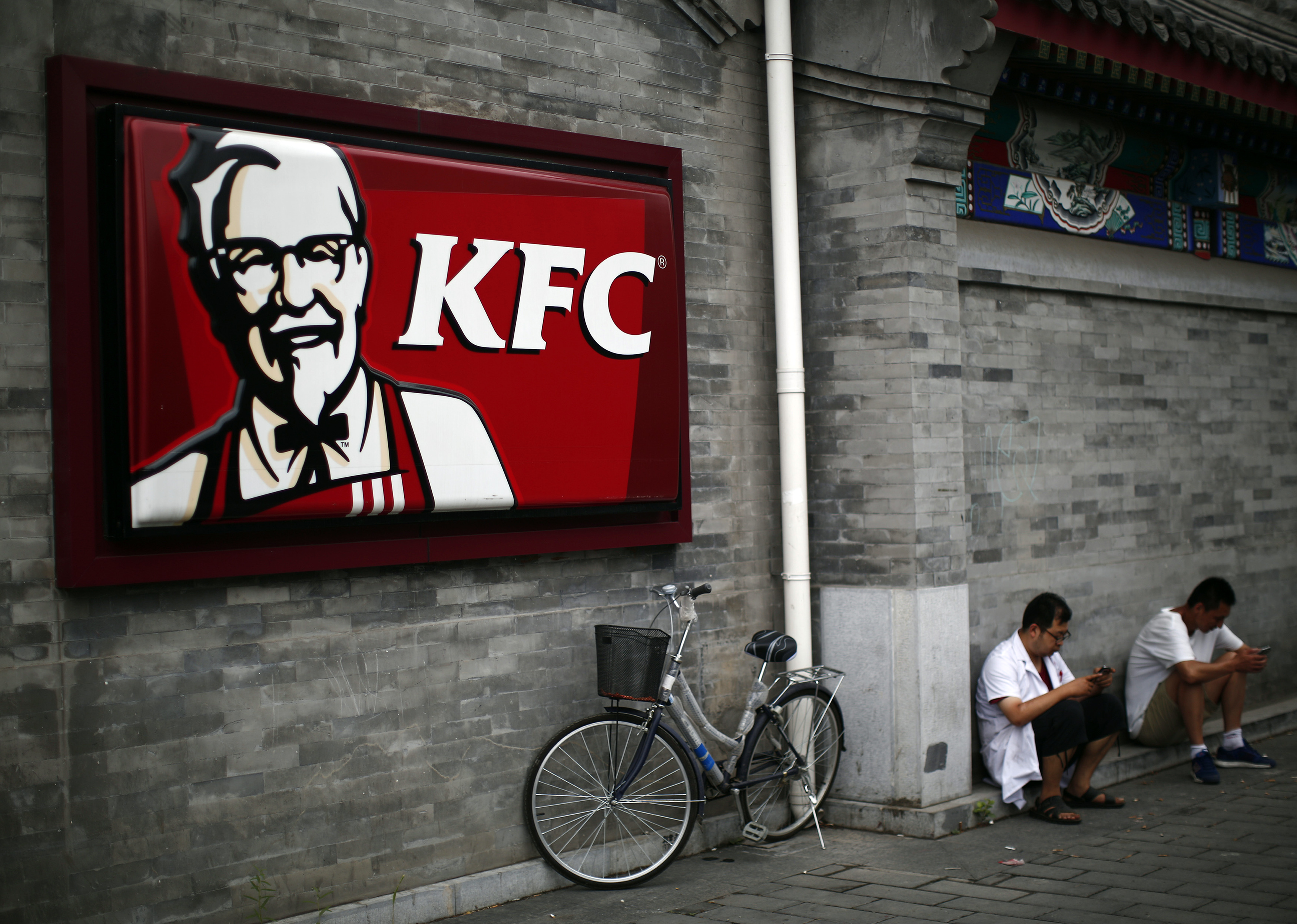 Men sits outside a KFC restaurant in Beijing
