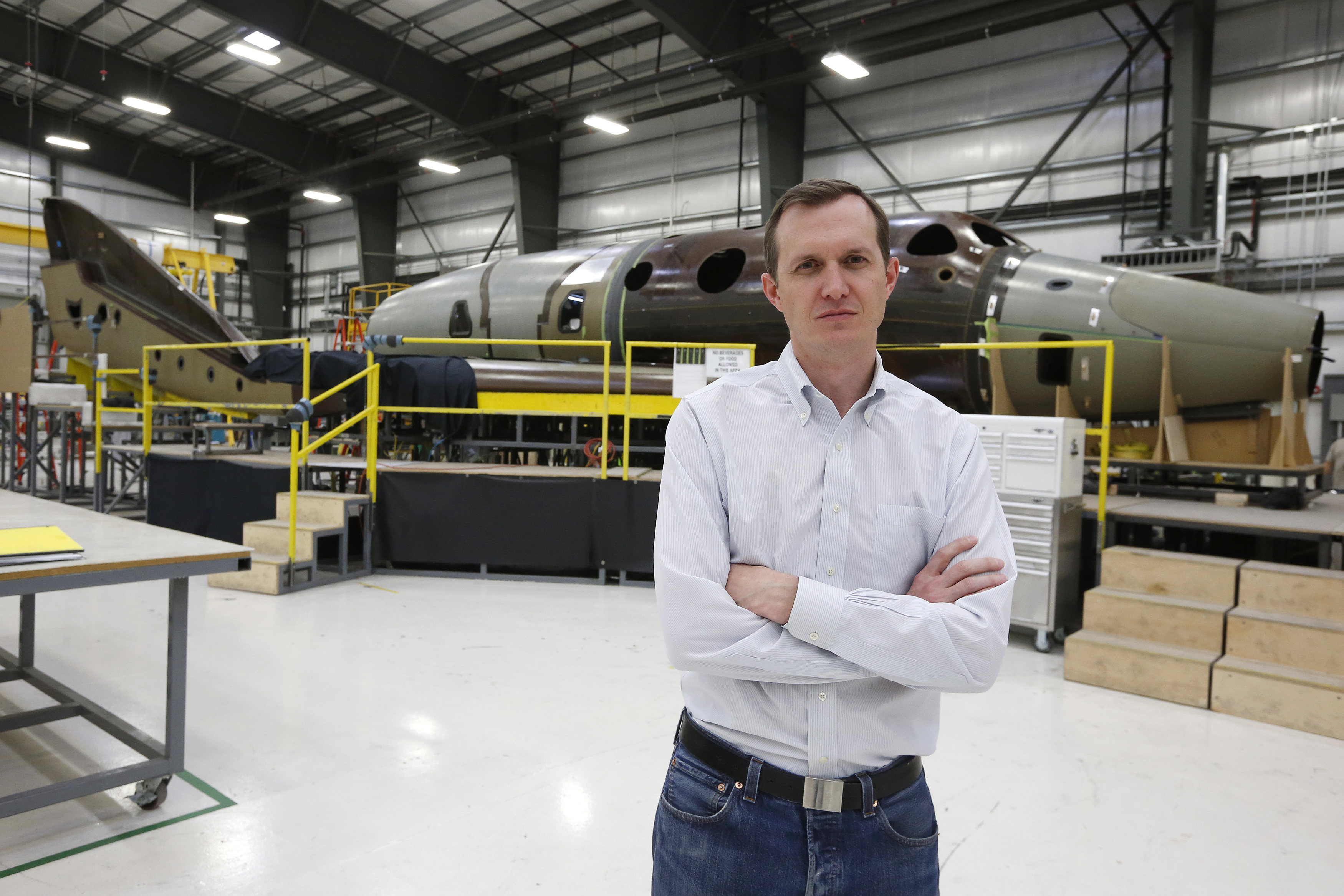 Virgin Galactic's CEO George T. Whitesides stands in front of their new spaceship N202VG, which the company began building 2 and a half years ago, in a hangar at Mojave Air and Space Port in Mojave, California
