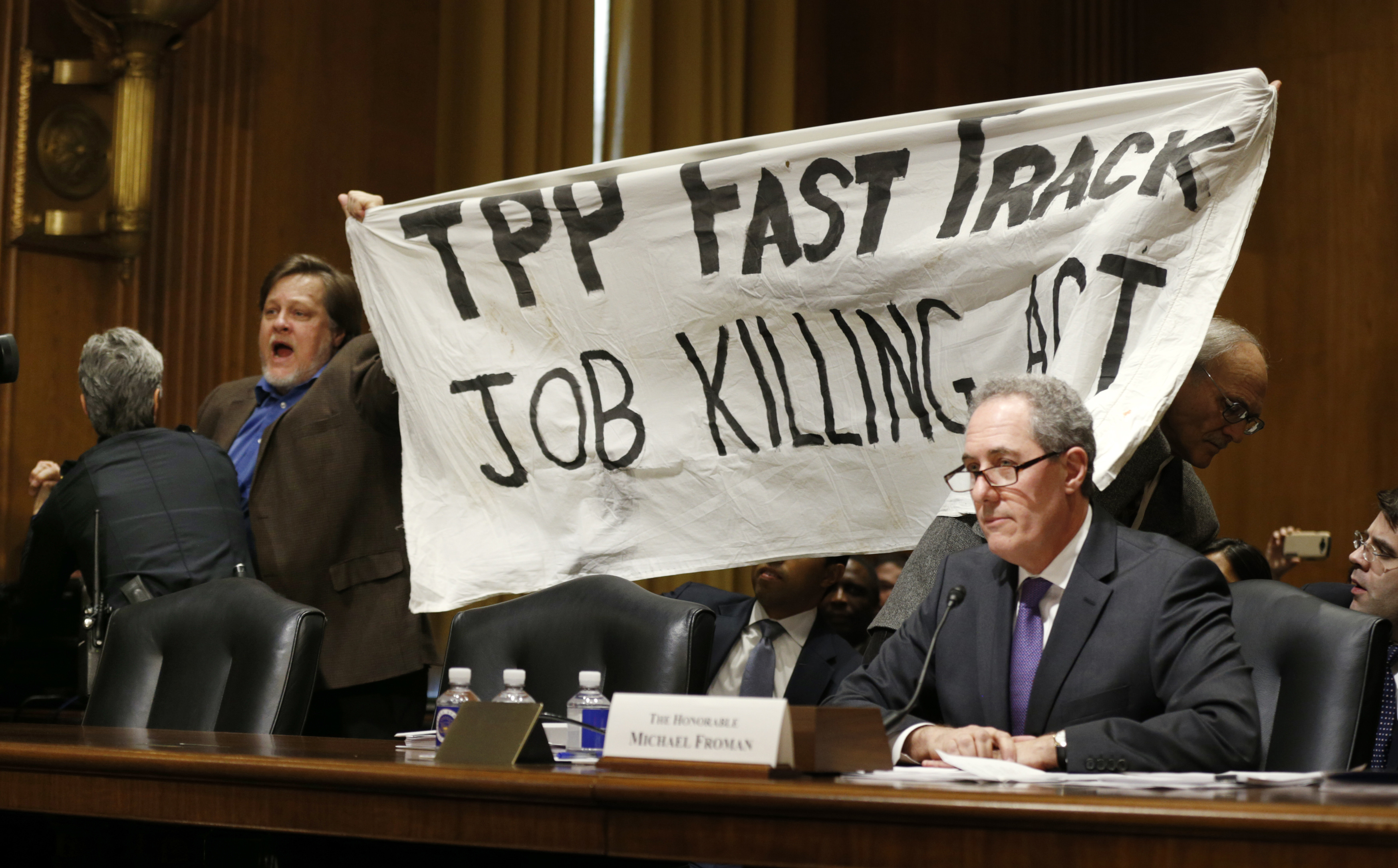 TPP protester holds up a sign during Froman trade hearing on Capitol Hill in Washington
