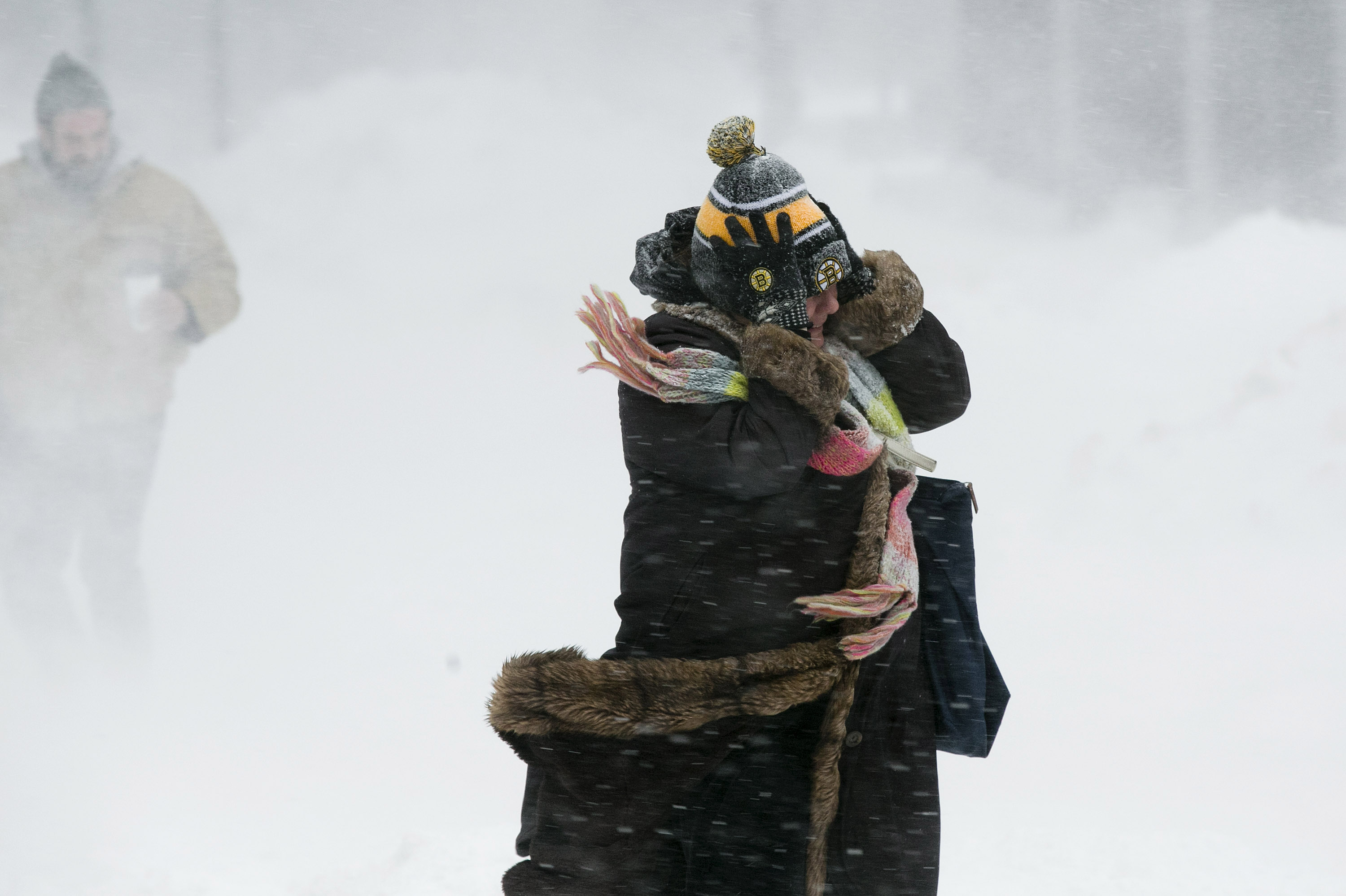 A woman holds onto her hat against the wind during a snow storm in Boston