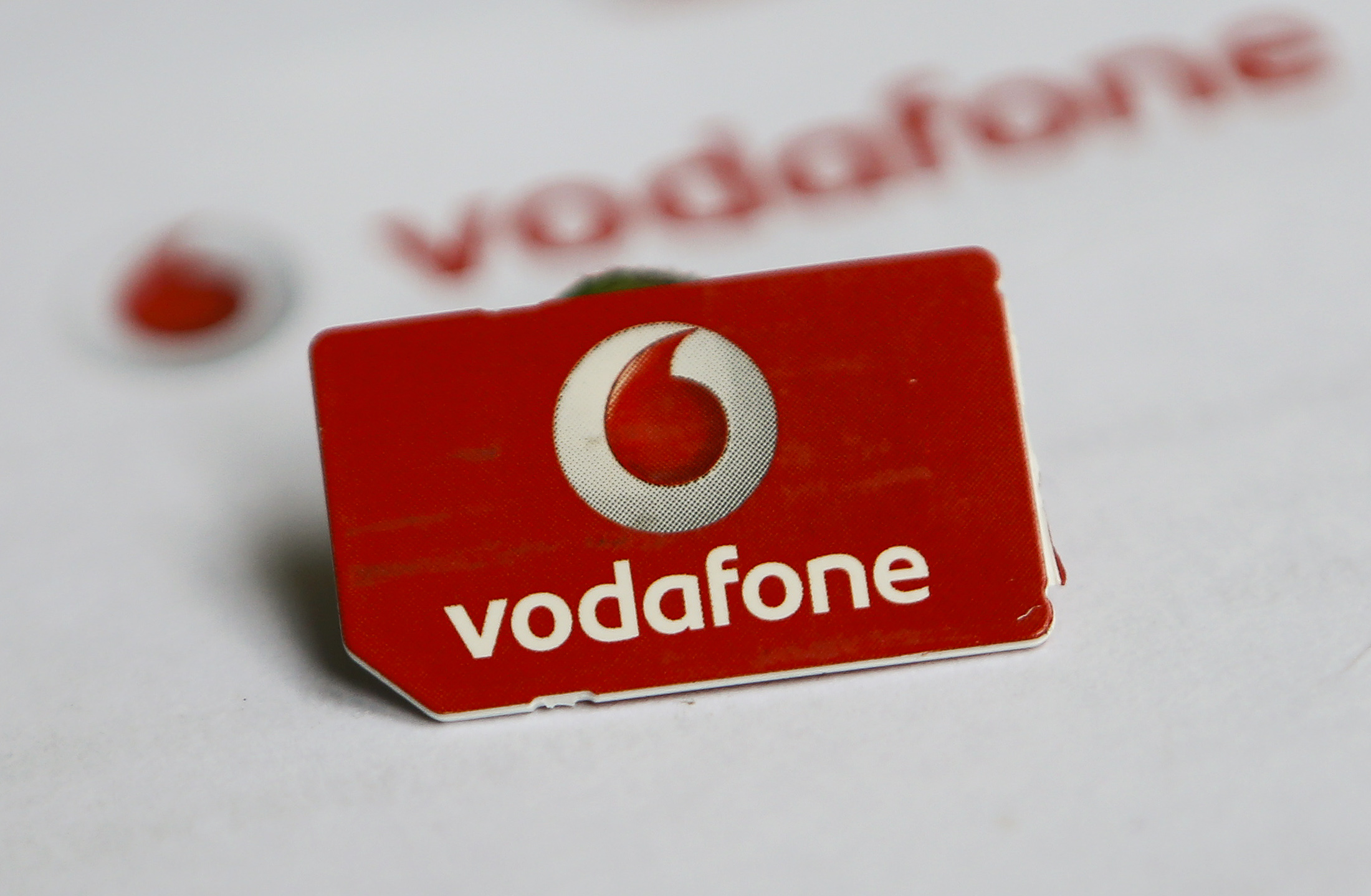 A SIM card of Vodafone is pictured in front of a letter of Vodafone in Dortmund