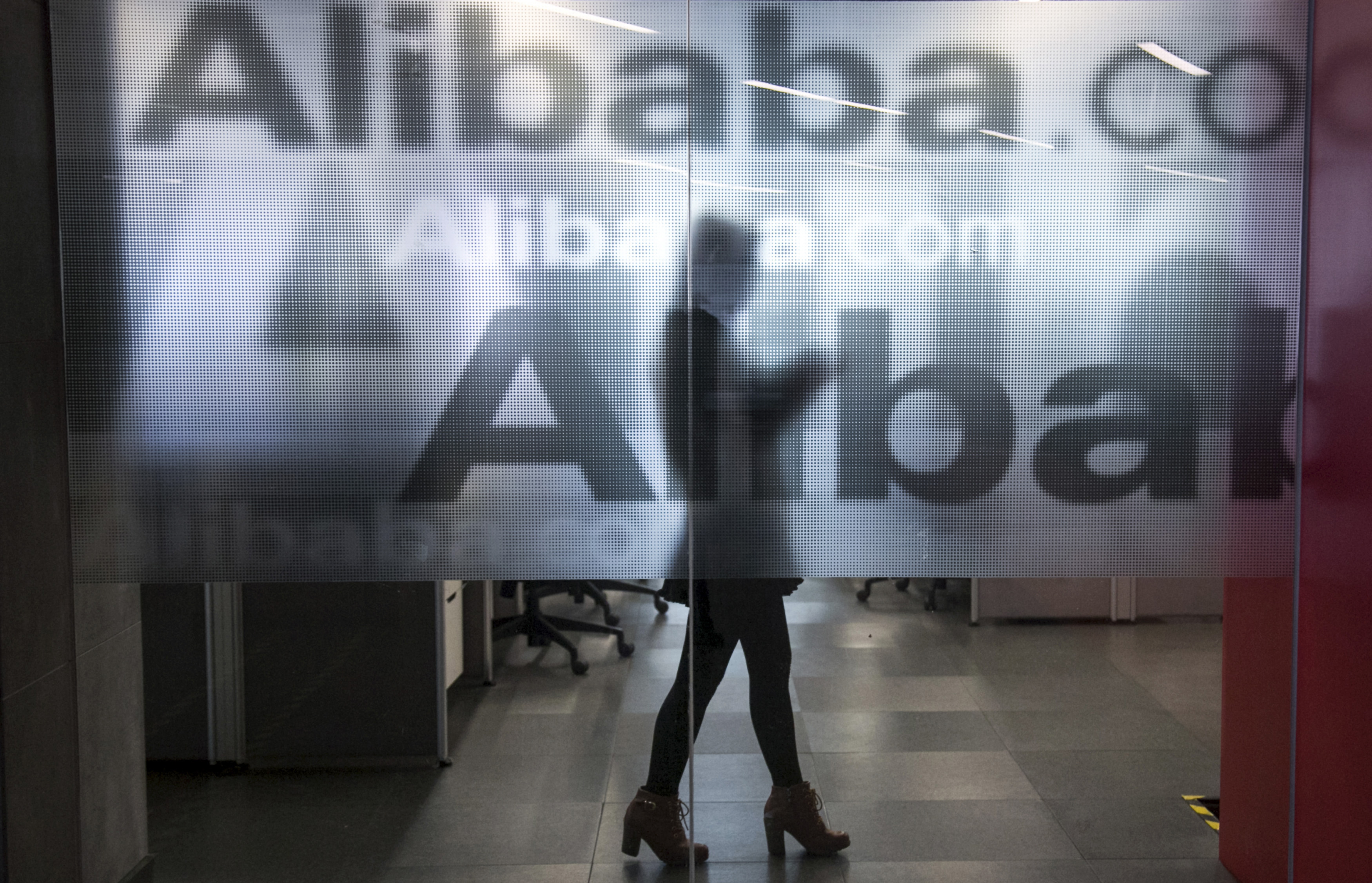 An employee is seen behind a glass wall with the logo of Alibaba at the company's headquarters on the outskirts of Hangzhou, Zhejiang province