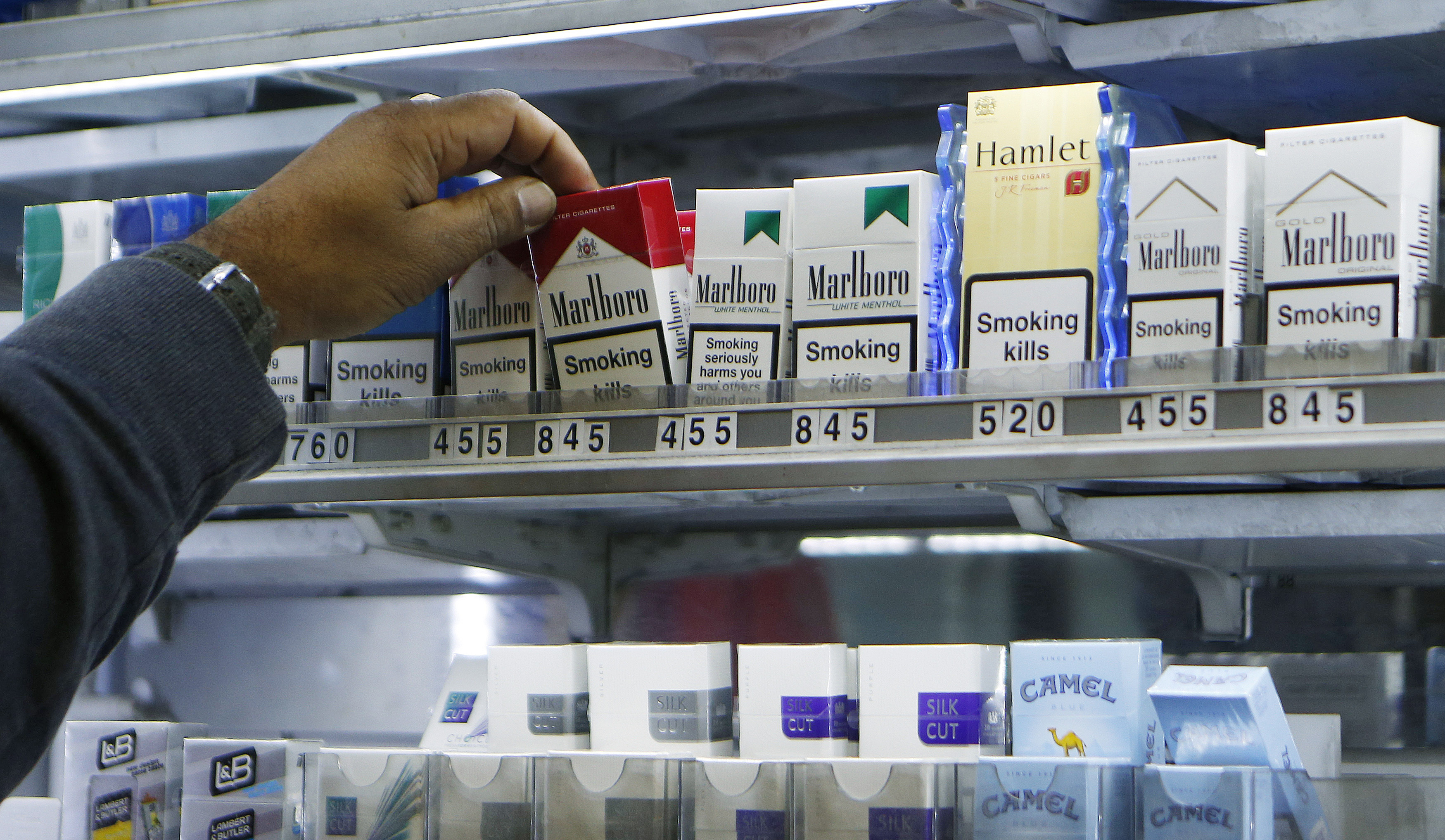 A shopkeeper reaches for a packet of cigarettes in a newsagent in London