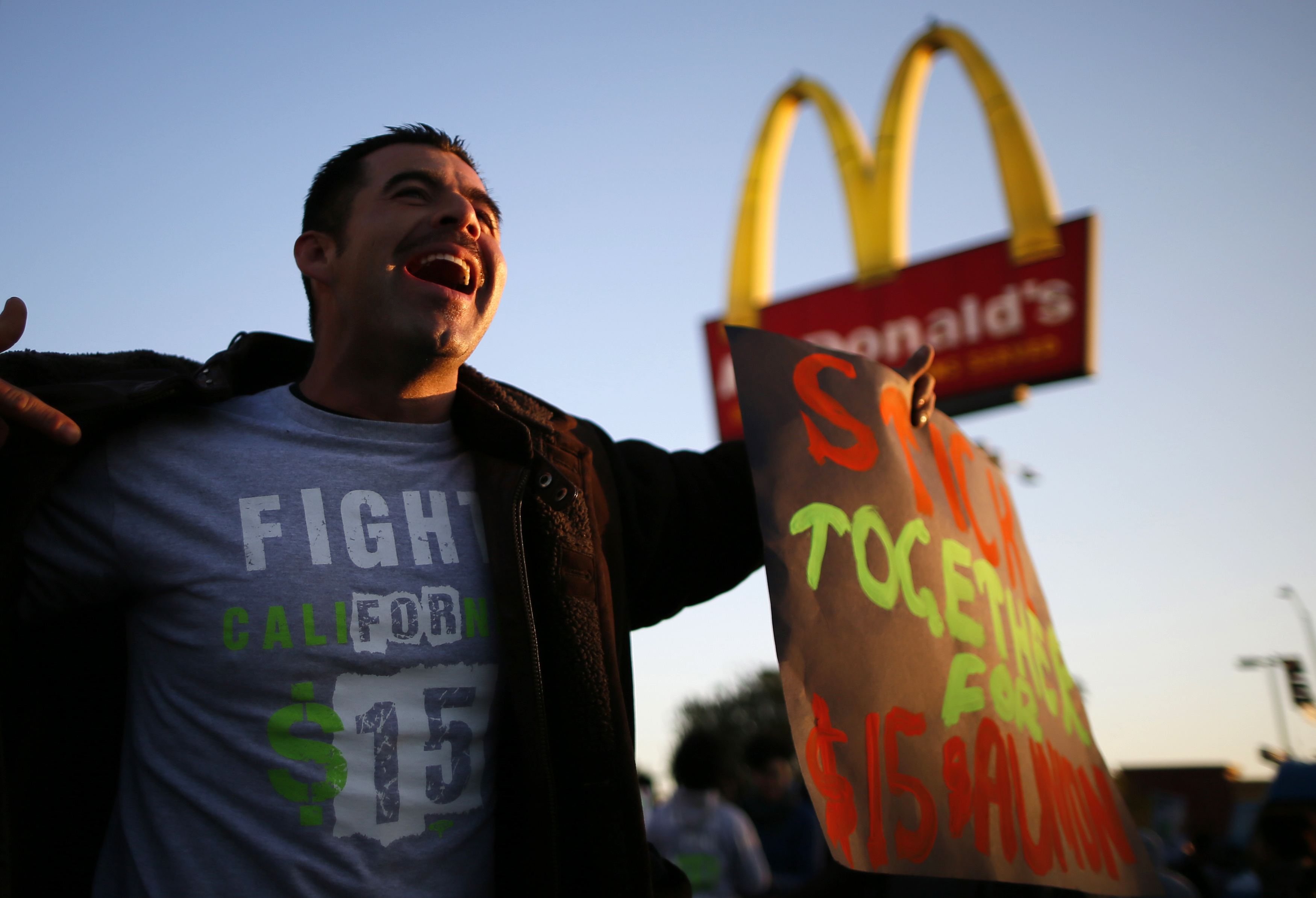 Striking McDonald's worker Abran Escarzaga, 31, protests outside McDonald's in Los Angeles