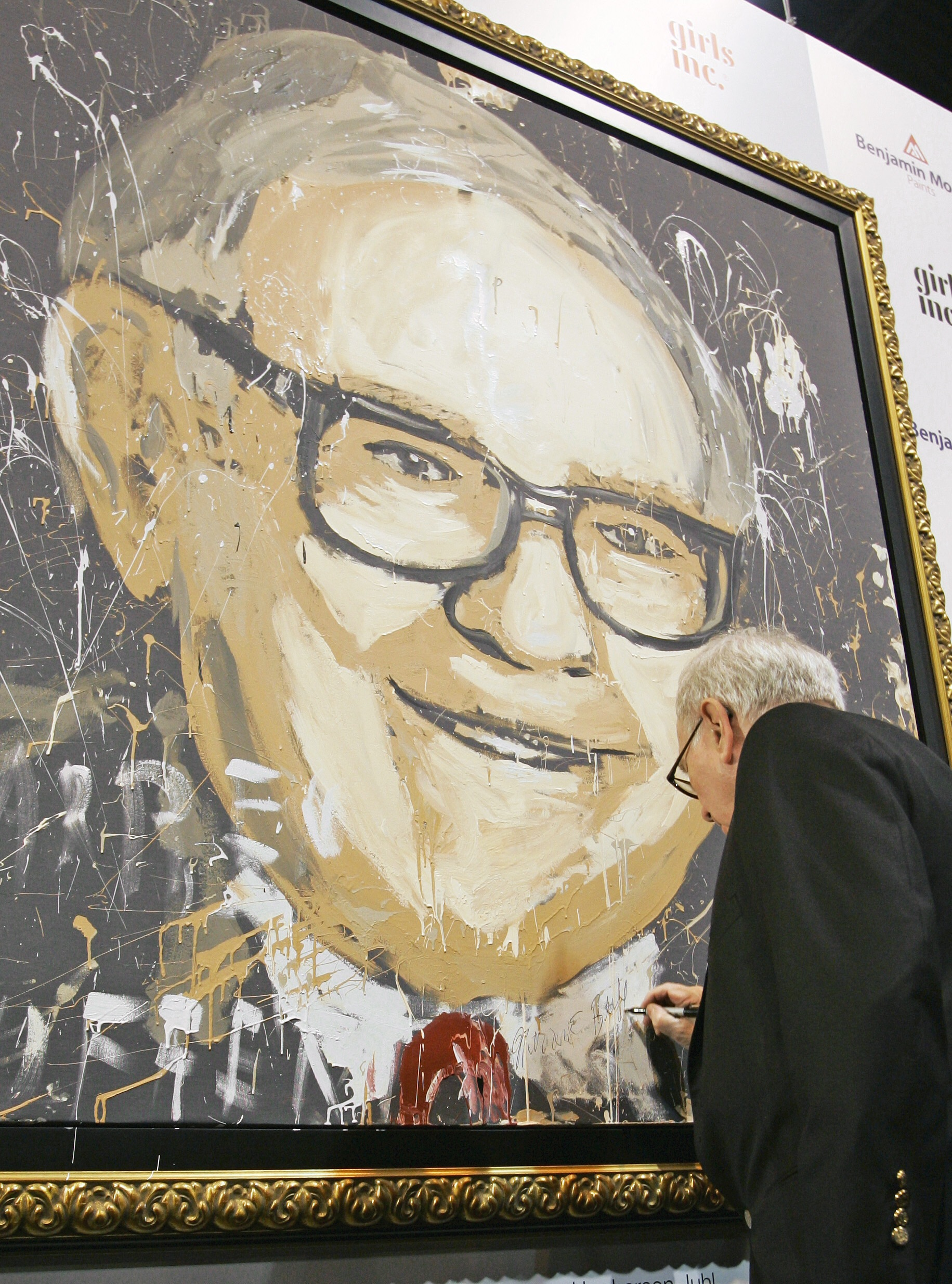 Warren Buffett signs a portrait of himself at the annual Berkshire Hathaway shareholders meeting, in Omaha, Nebraska on May 3, 2008.