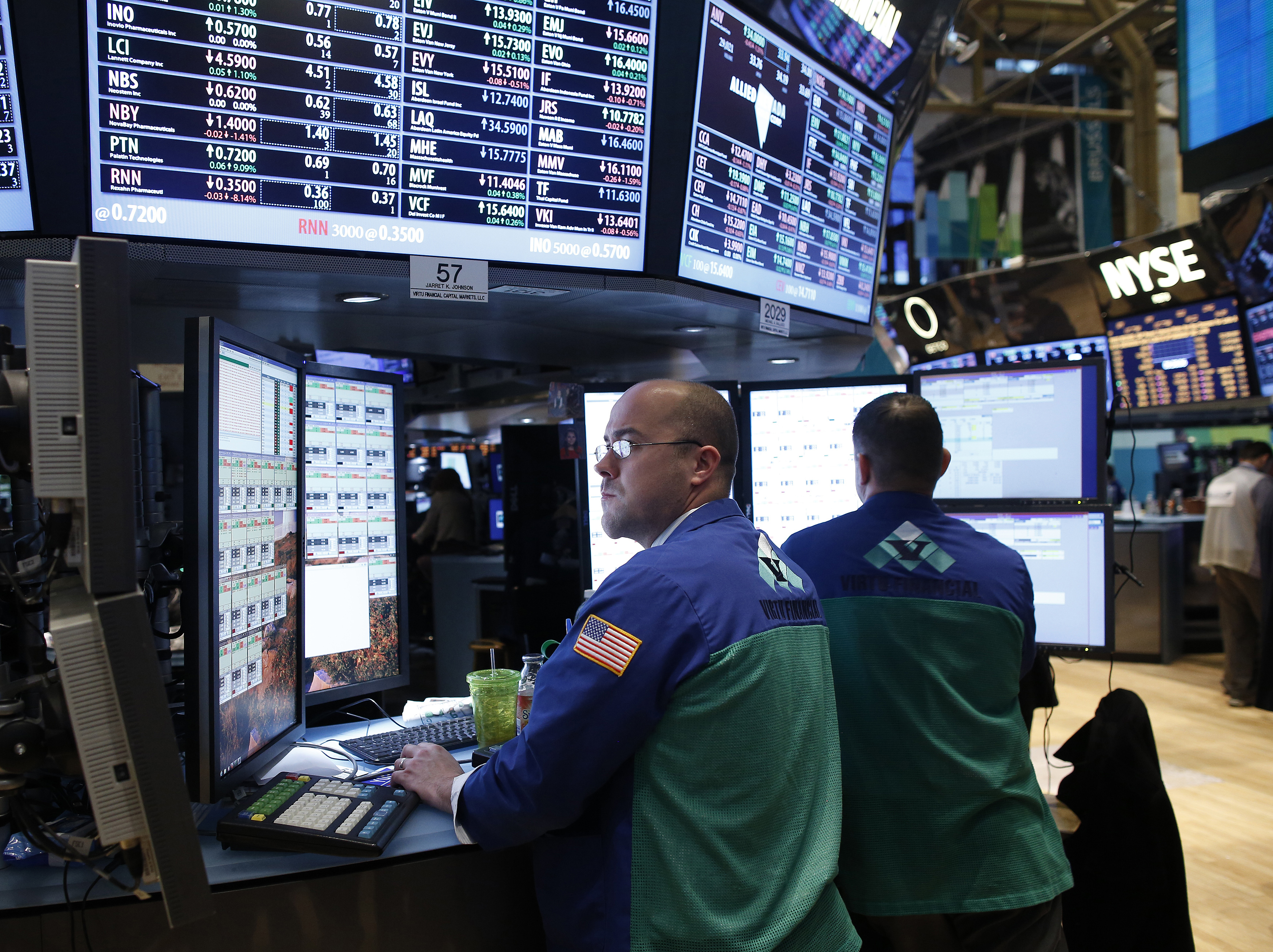 Trader Jarret Johnson of Virtu Finalcial looks at multiple computer monitors while working at a newly renovated section of trading stations on the floor of the New York Stock Exchange