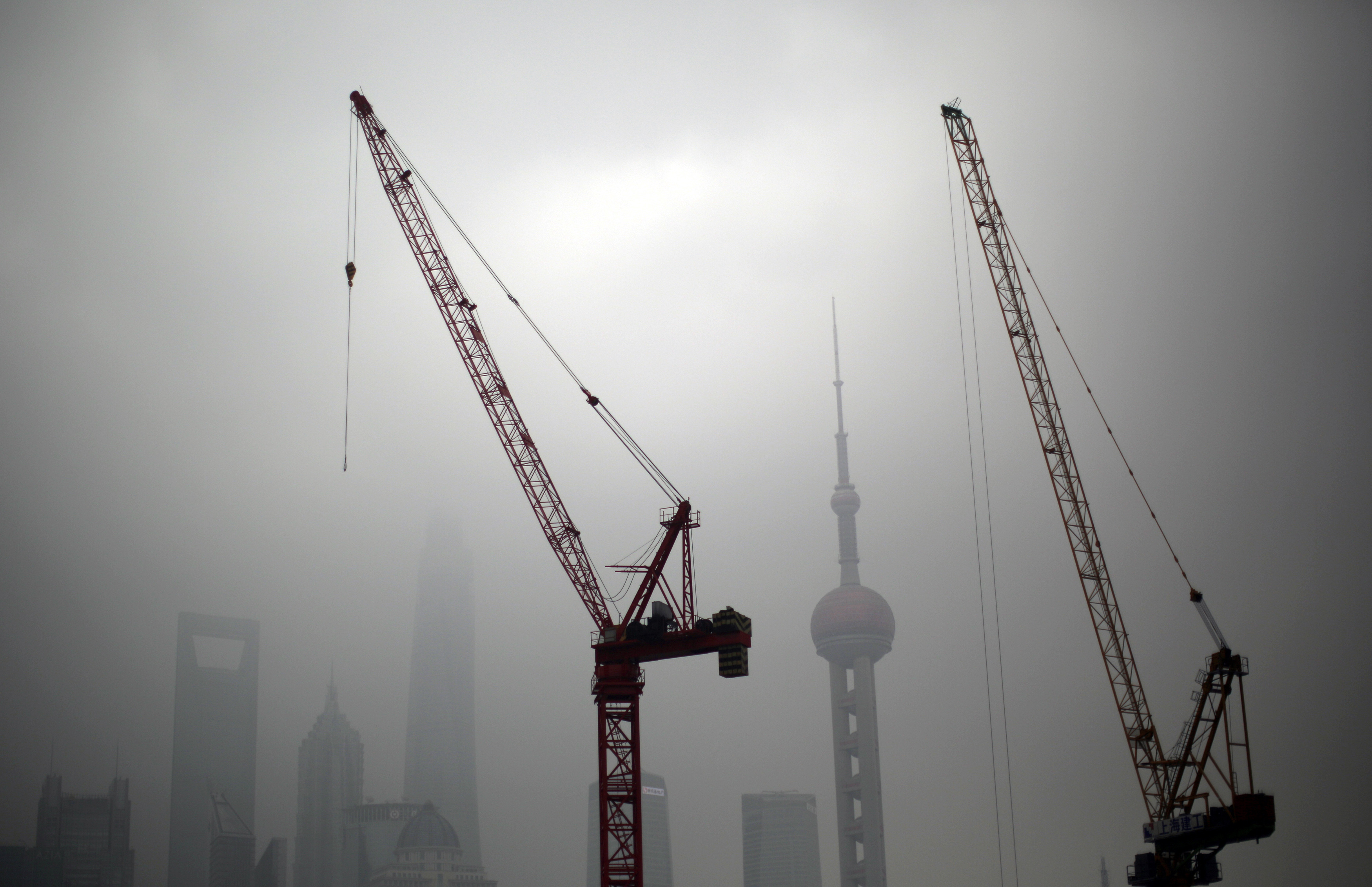 Construction cranes are see near Pudong financial district of Shanghai