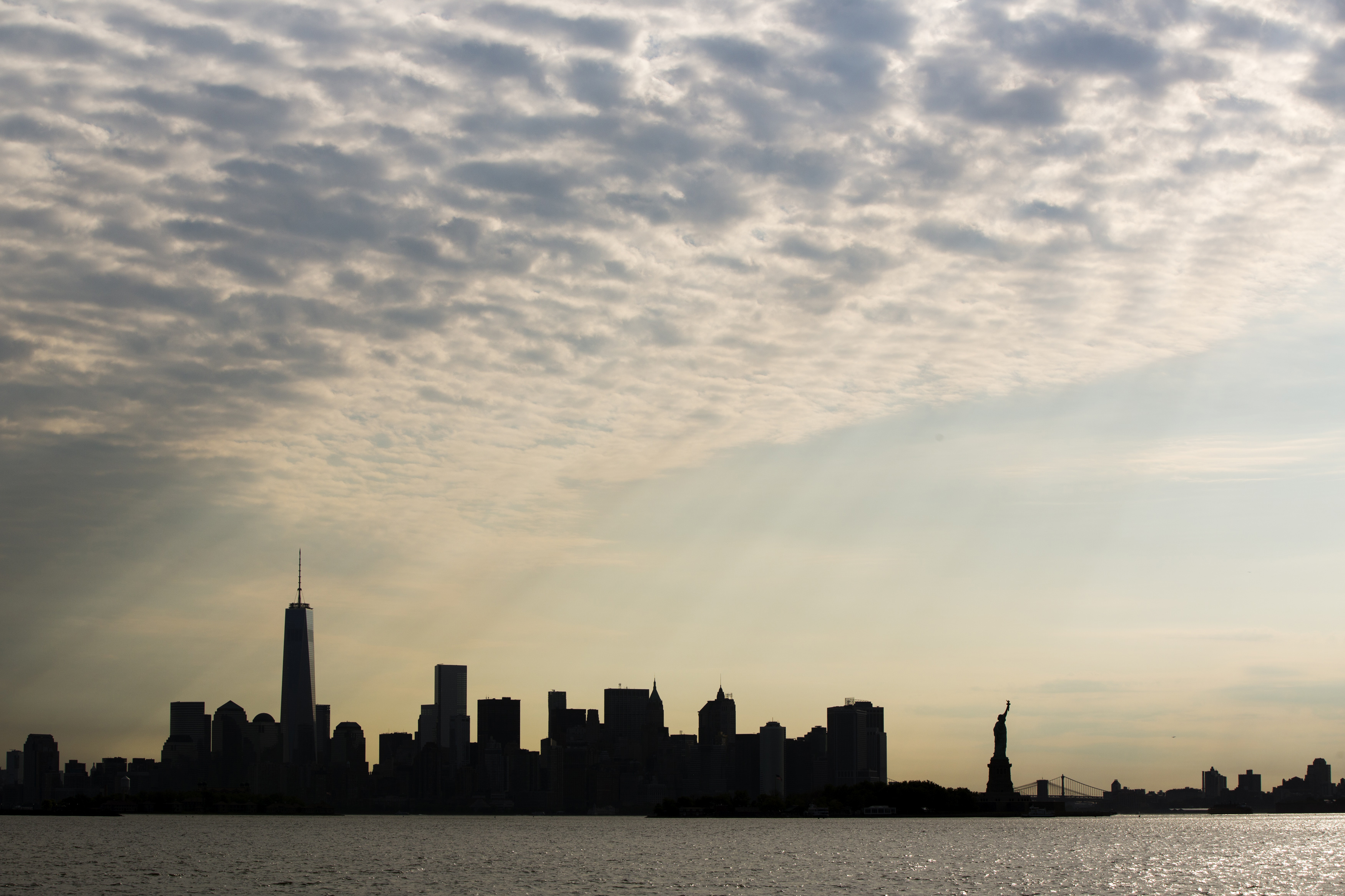 The sun rises behind the Statue of Liberty and the skyline of lower Manhattan in New York