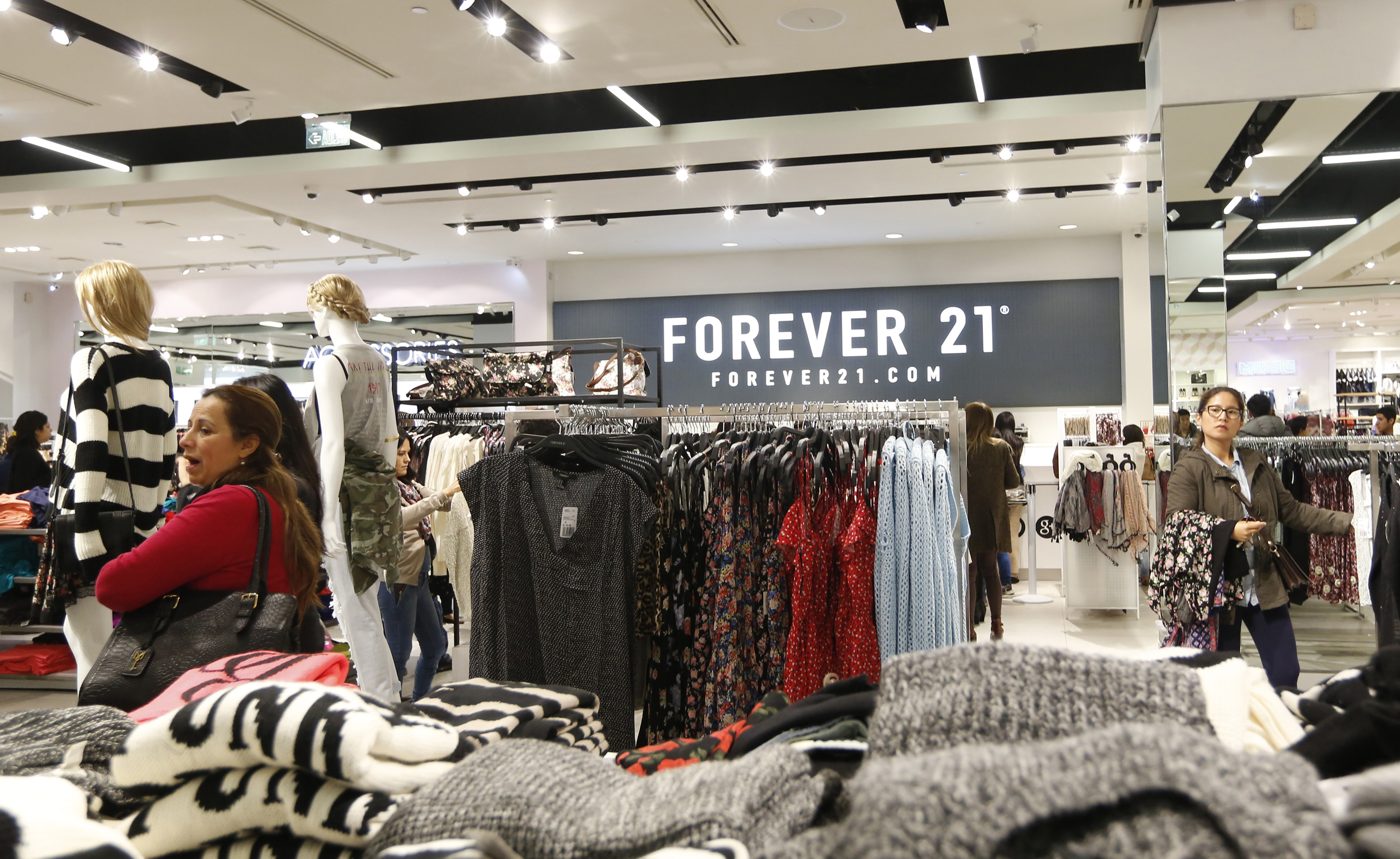 Customers browse through clothes at the first Forever 21 retail store in Lima, at Real Plaza Salaverry shopping mall