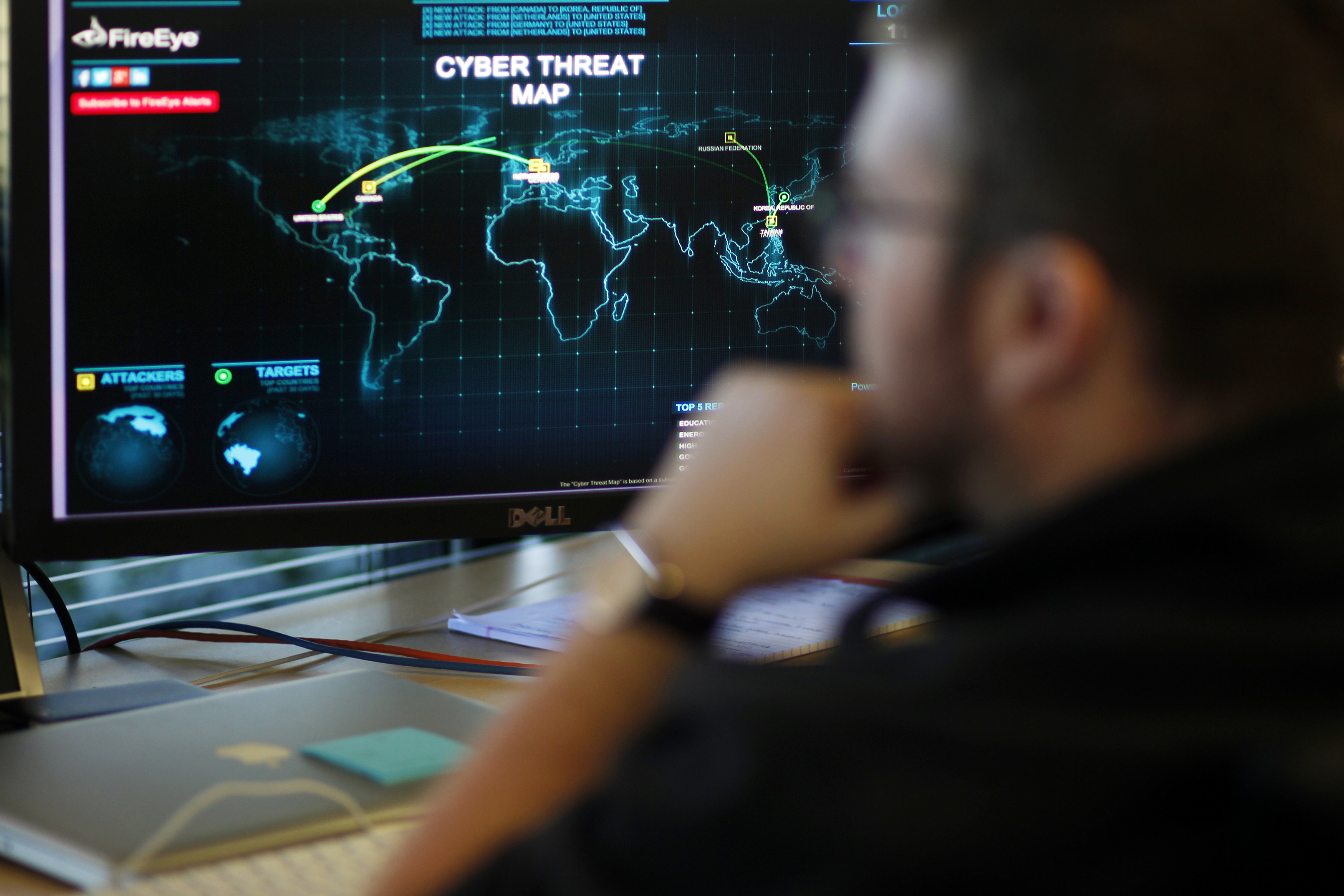 FireEye information analyst works in front of a screen showing a near real-time map tracking cyber threats at the FireEye office in Milpitas, California