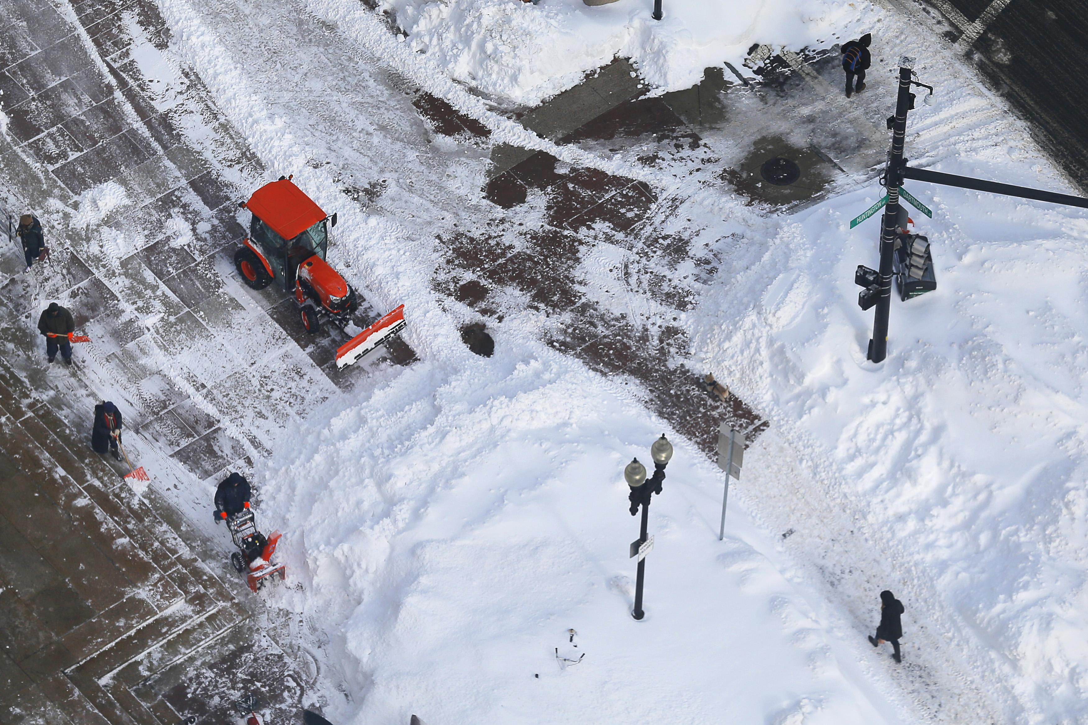 Crews work to clear sidewalks following a winter blizzard in Boston