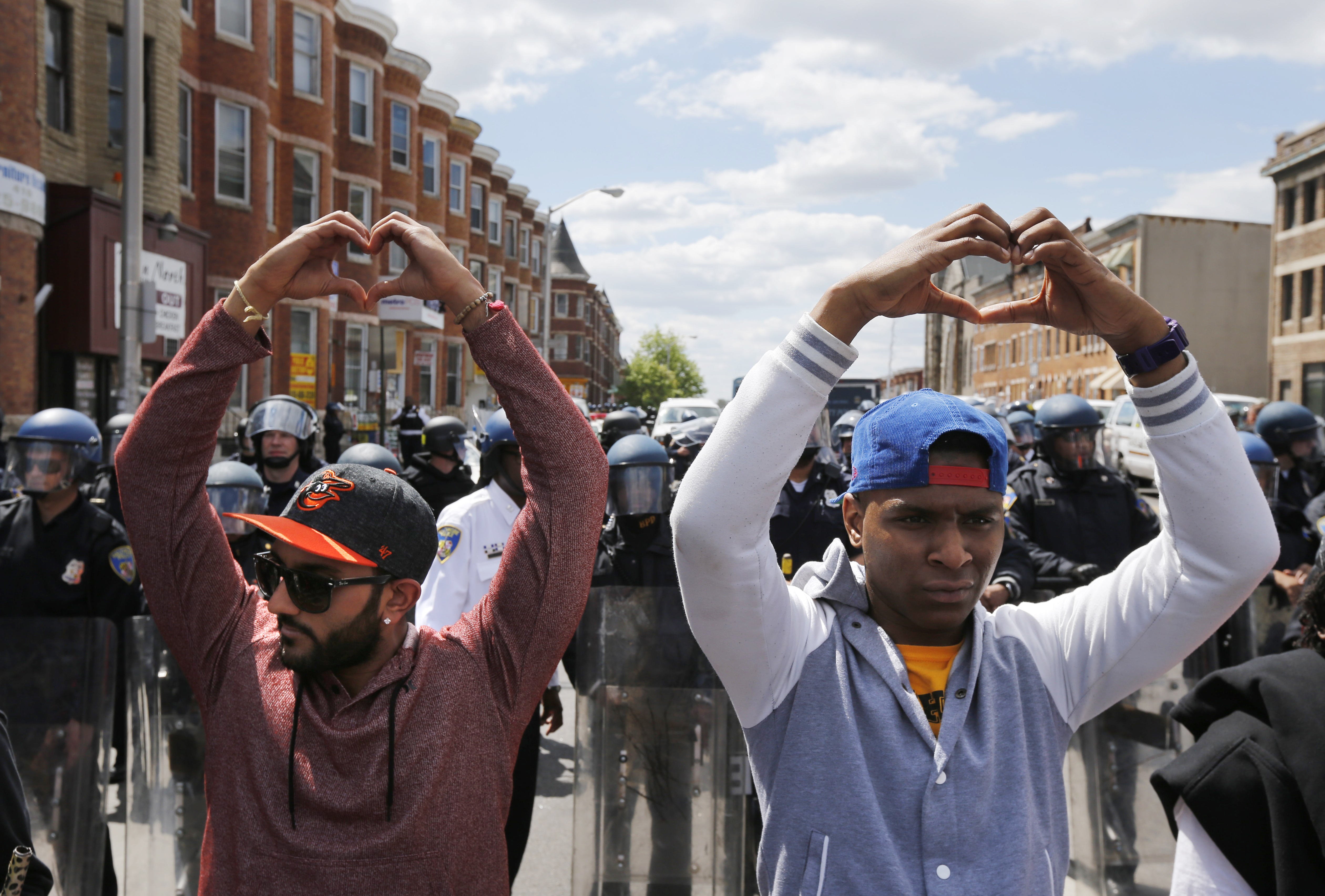 Members of the community make heart gestures with their hands in front of a line of police officers in riot gear, near a recently looted and burned CVS store in Baltimore