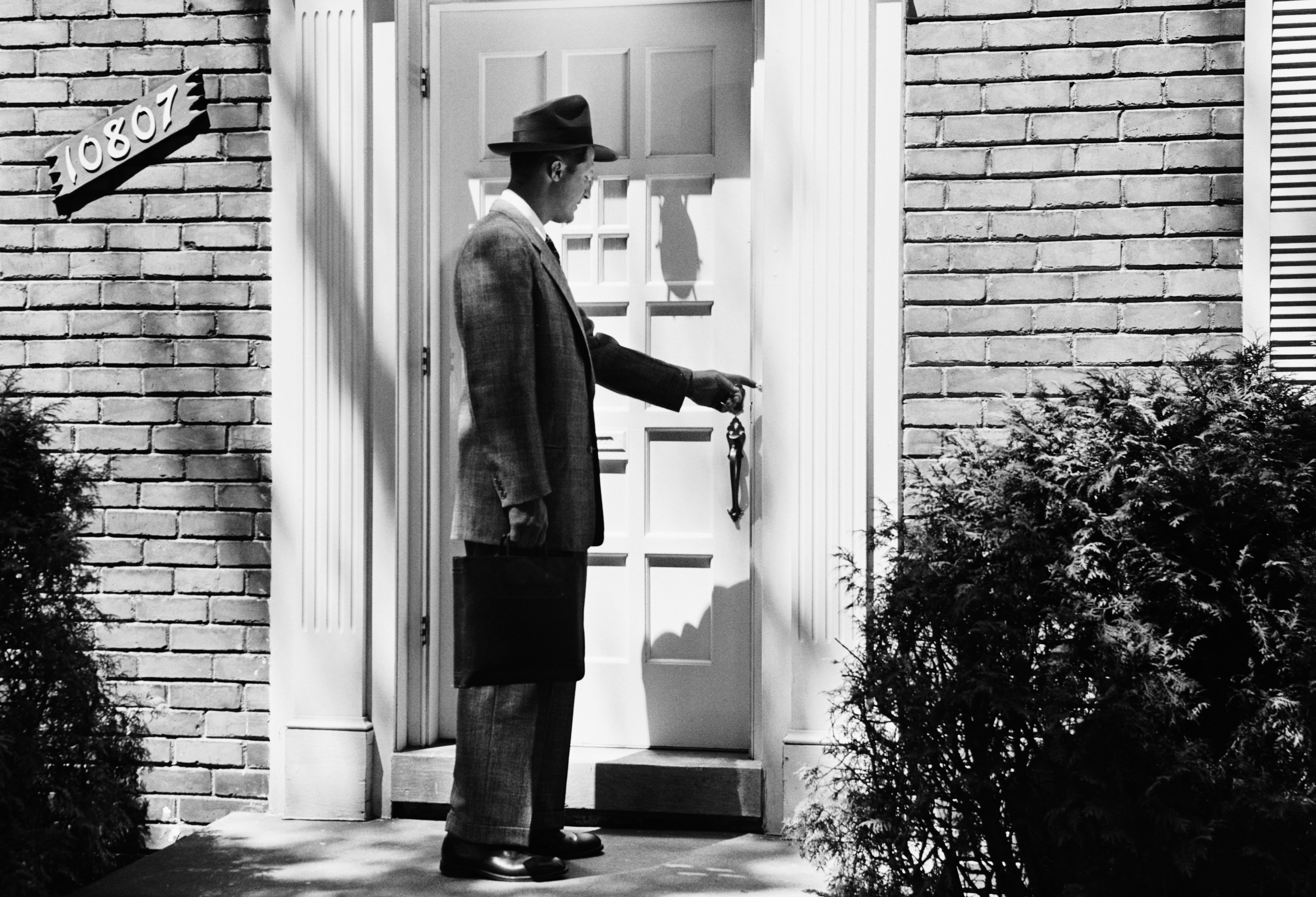 A man ringing the doorbell of a house in 1952.