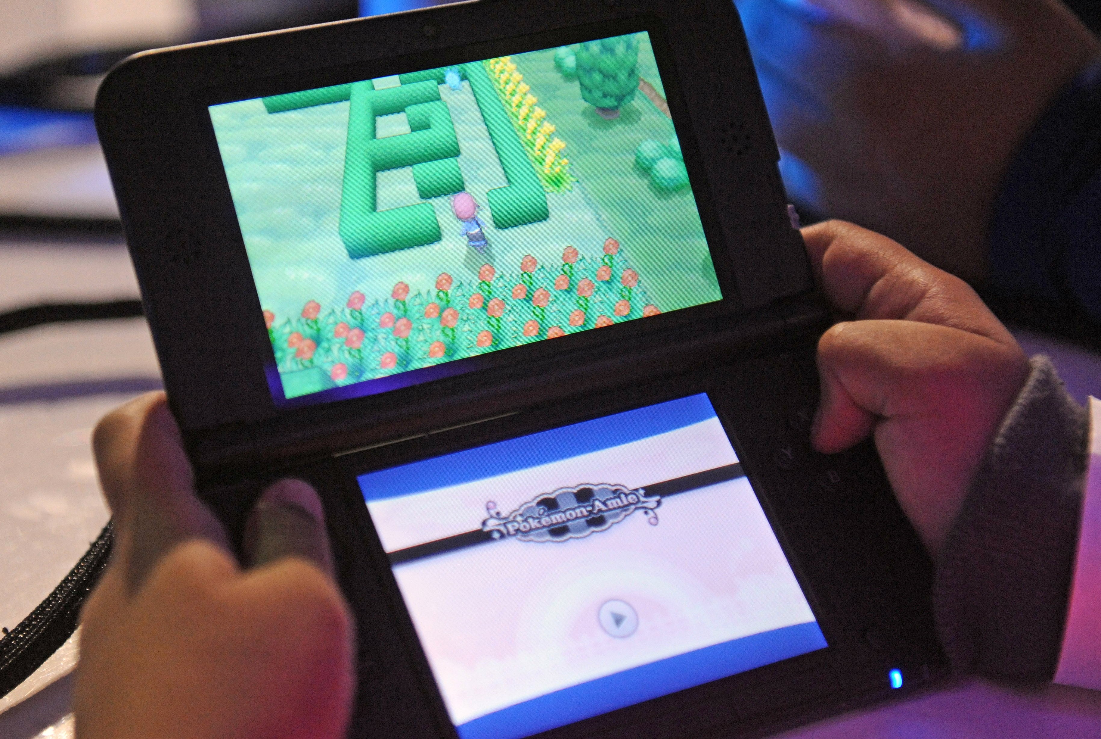 Attendees play a demo version of Pokemon X and Pokemon Y on the Nintendo 3DS at one of several kiosks  in New York on Friday, Oct. 11, 2013.The event celebrates the release of the two new games. Photographer: Louis Lanzano/ Bloomberg *** Local Caption *** Nintendo