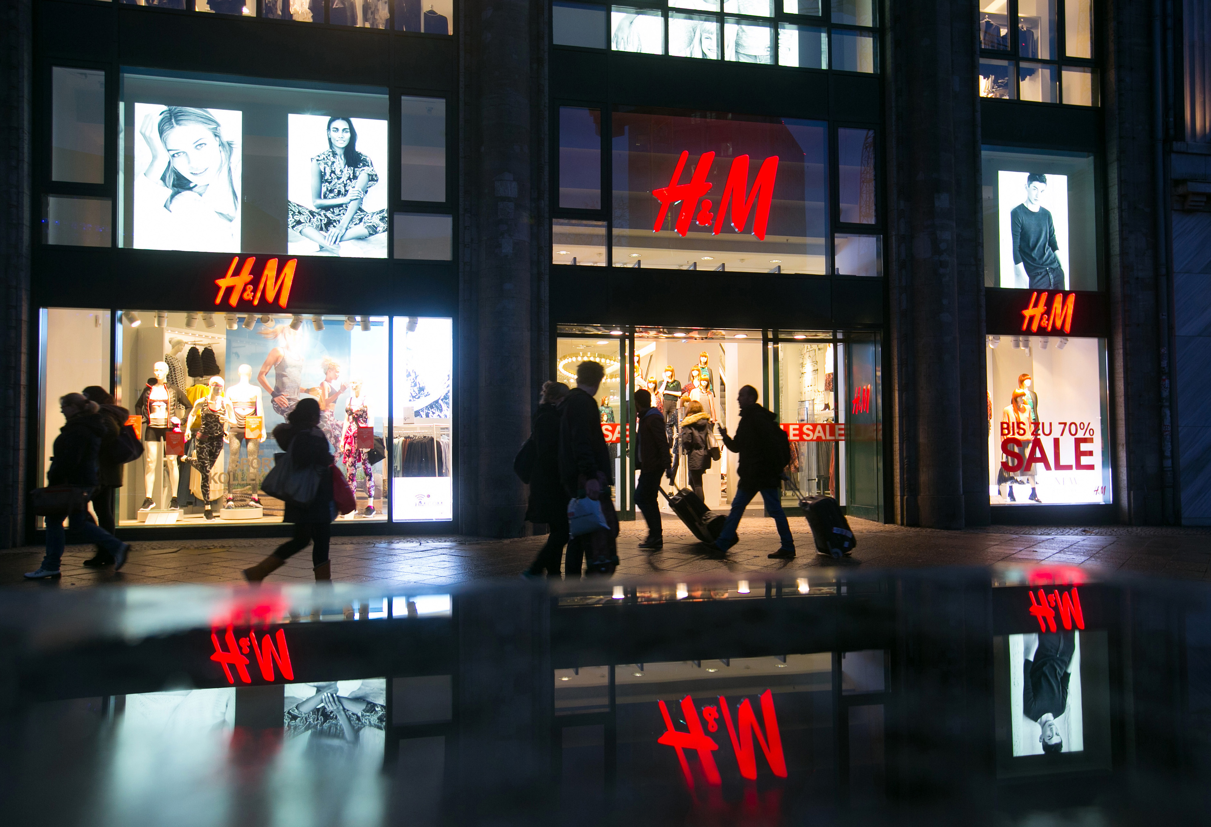 Pedestrians pass an illuminated Hennes & Mauritz AB (H&M) clothing fashion store in Berlin, Germany, on Wednesday, Jan. 7, 2014. As European Central Bank policy makers gather for their first meeting of 2015 today, the backdrop is a 0.2 percent annual drop in consumer prices, the first in more than five years. Photographer: Krisztian Bocsi/Bloomberg