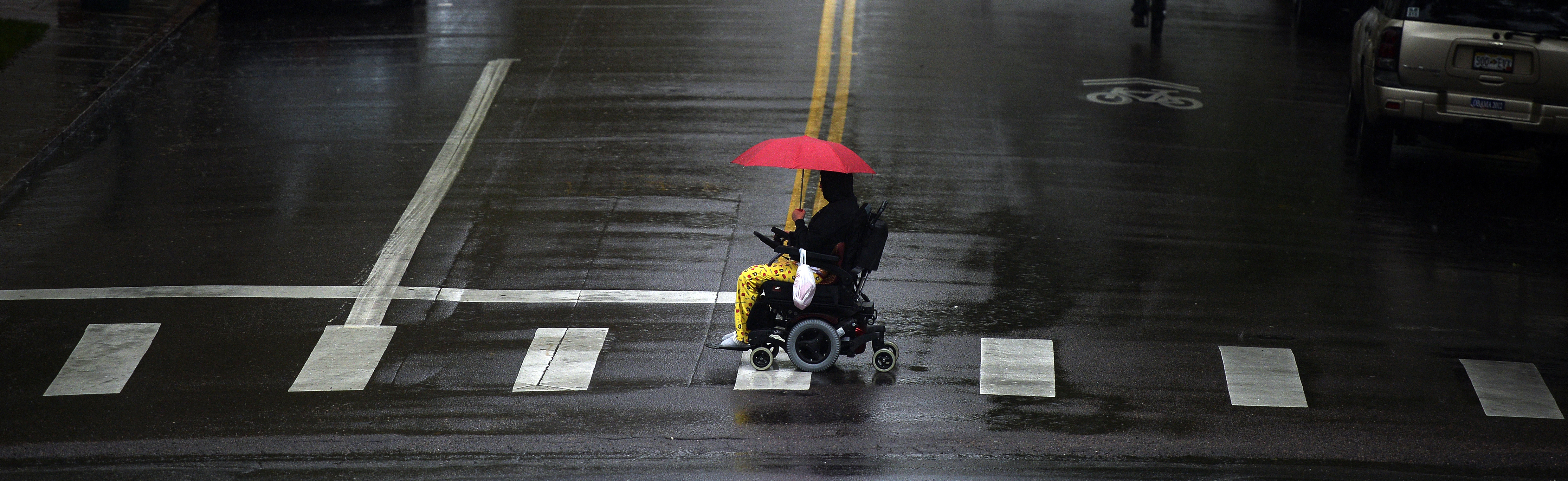 A person in a wheelchair has a red umbrella for protection as they cross Sherman Street at Colfax Ave across from the state capitol  in Denver on a rainy Tuesday.