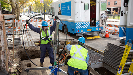 Two Con Edison employees work on underground electrical delivery equipment in New York City.
