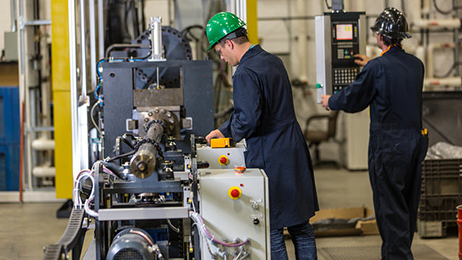 Technicians ensure precise elastometric geometry when injecting the stator for a progressing cavity pump at a Dover Artificial Lift facility in Calgary, Canada.