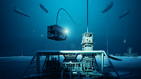 Subsea production equipment being installed and serviced. In the foreground, a Remotely Operated Vehicle (ROV) oversees well intervention operations on a subsea production tree.