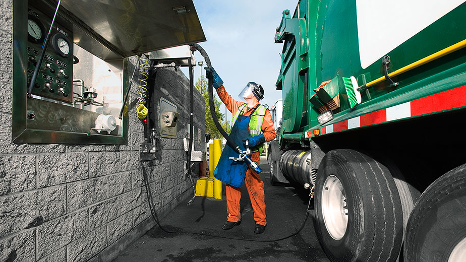 A worker fuels a WM truck with methane in Oakland.