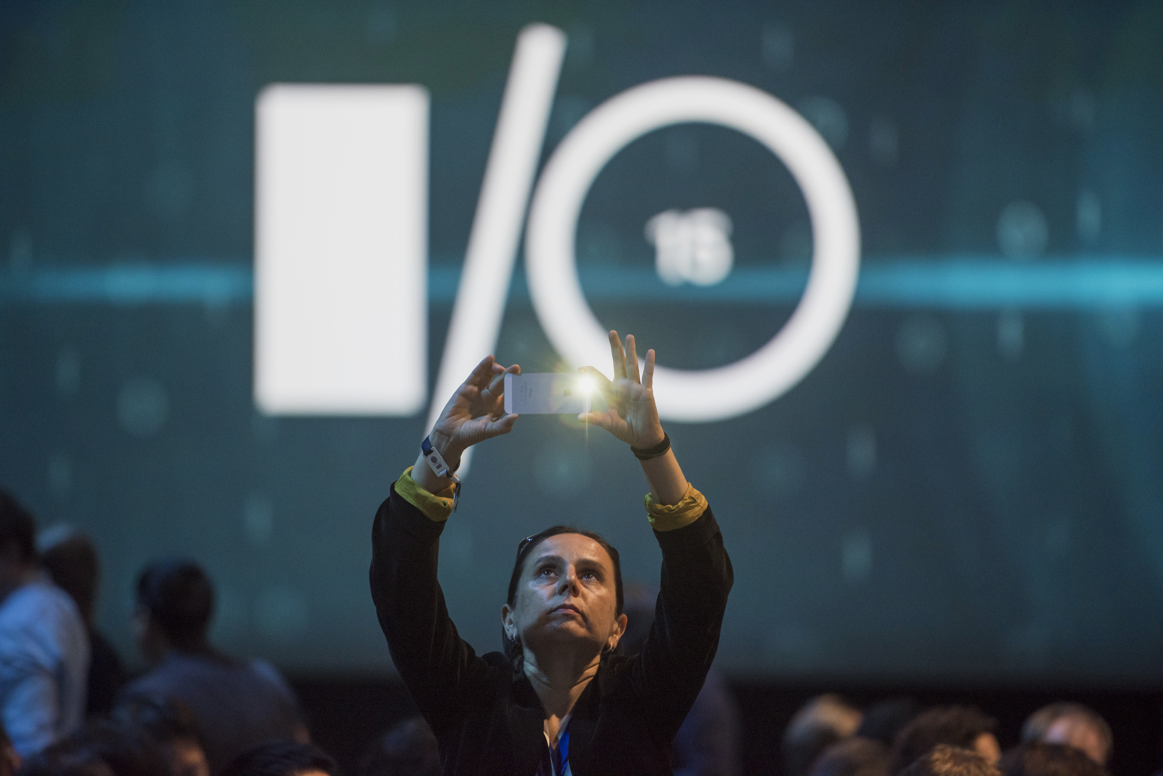 An attendee takes a photograph prior to the Google I/O Annual Developers Conference in San Francisco, California, U.S., on Thursday, May 28, 2014. Google Inc. executives are taking the stage this week to talk about a plethora of new technologies, including automobiles, home automation, digital TV, Web-connected devices and a new version of Android. Photographer: David Paul Morris/Bloomberg