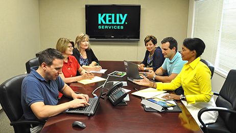 A group of employees in the Kelly Services conference room.