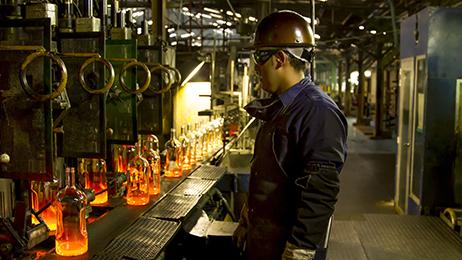 Owens Illinois Soacha Flint bottles exiting forming machine.