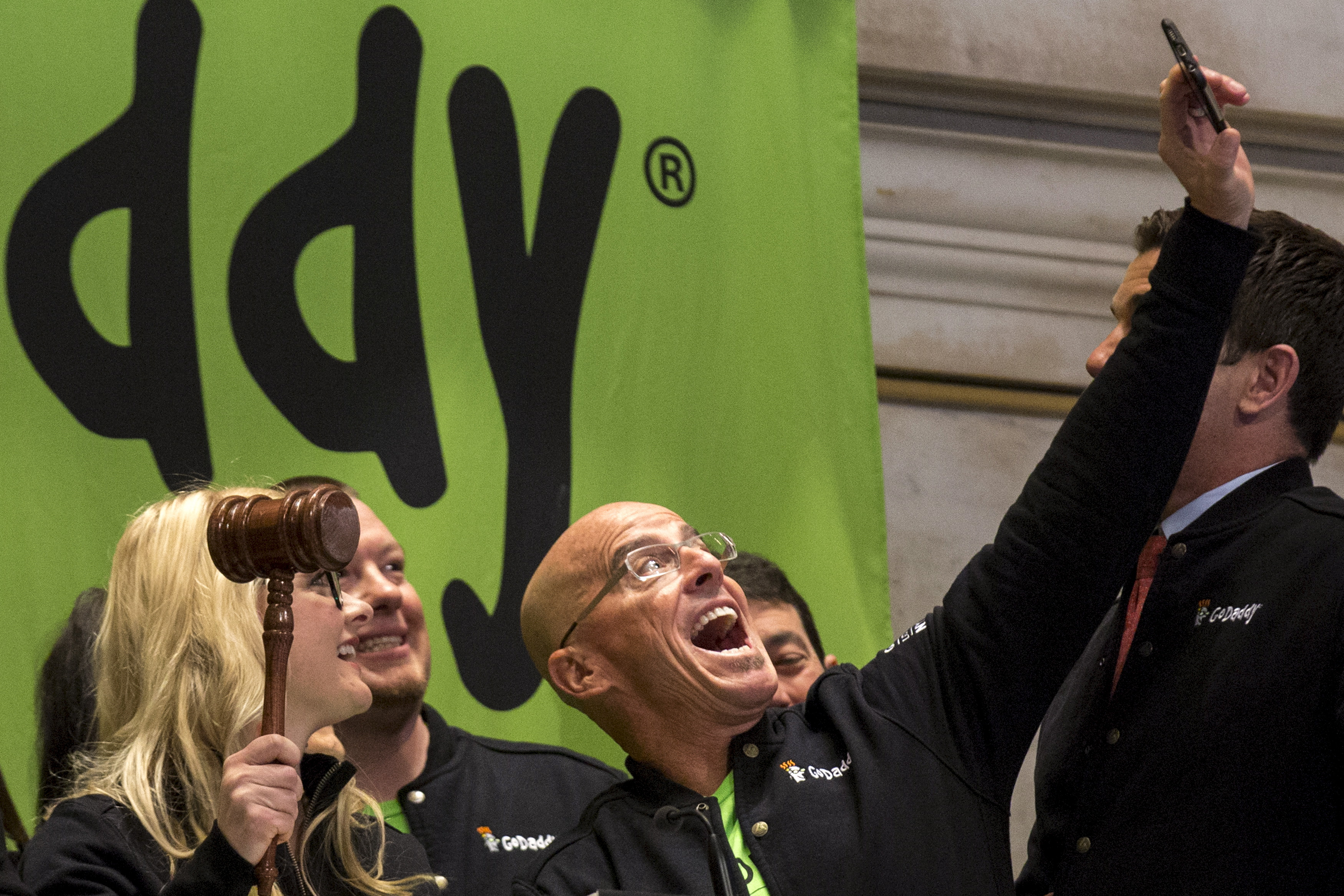 "GoDaddy CEO Blake Irving takes ""selfie"" photo with a customer before they ring the opening bell to celebrate his web hosting company GoDaddy's IPO on the floor of the New York Stock Exchange"