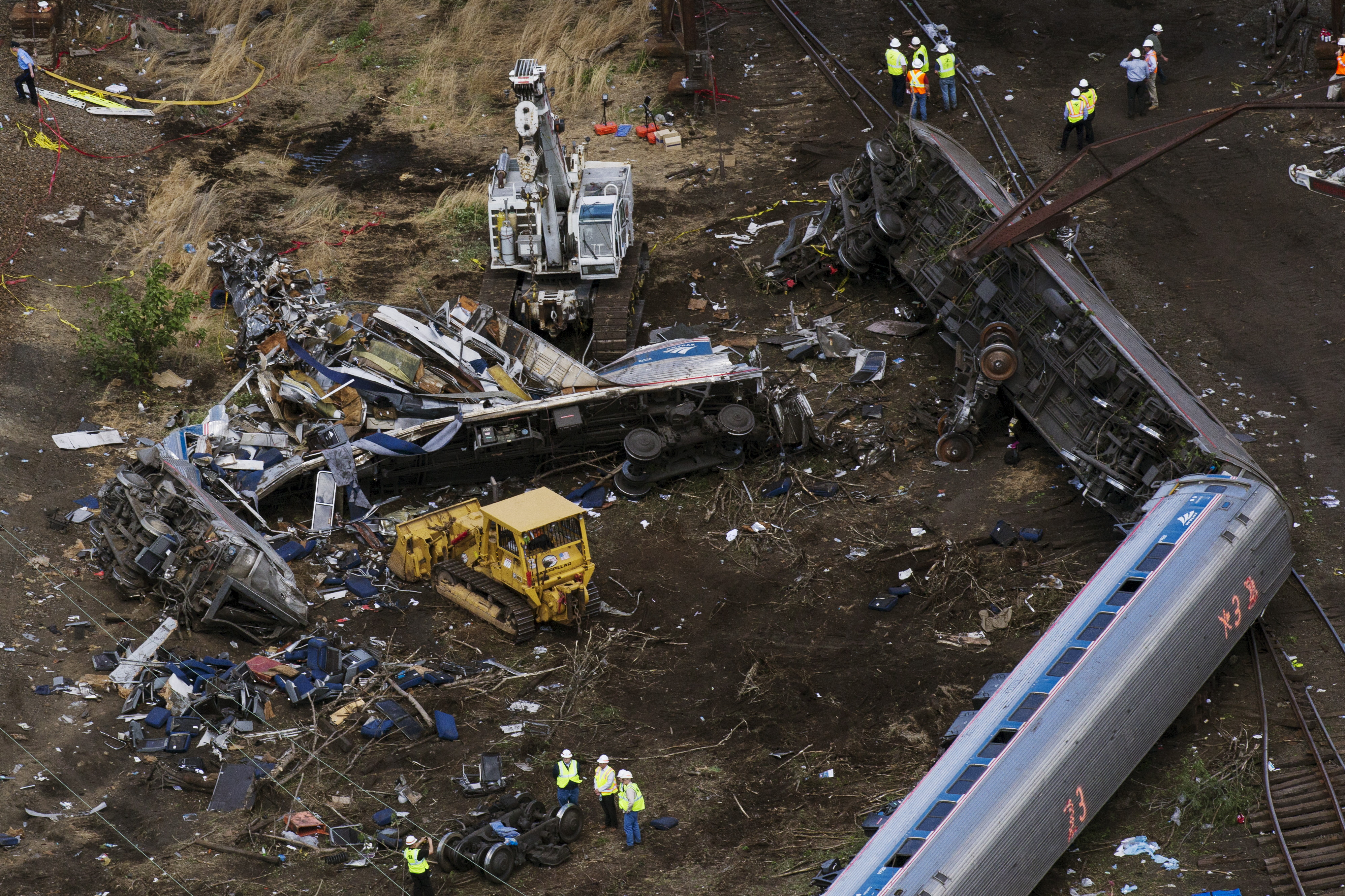 Emergency workers and Amtrak personnel inspect a derailed Amtrak train in Philadelphia, Pennsylvania