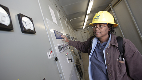 A technician at AES' Indianapolis Power & Light Company, reviews readings on amp meters and protective relays.