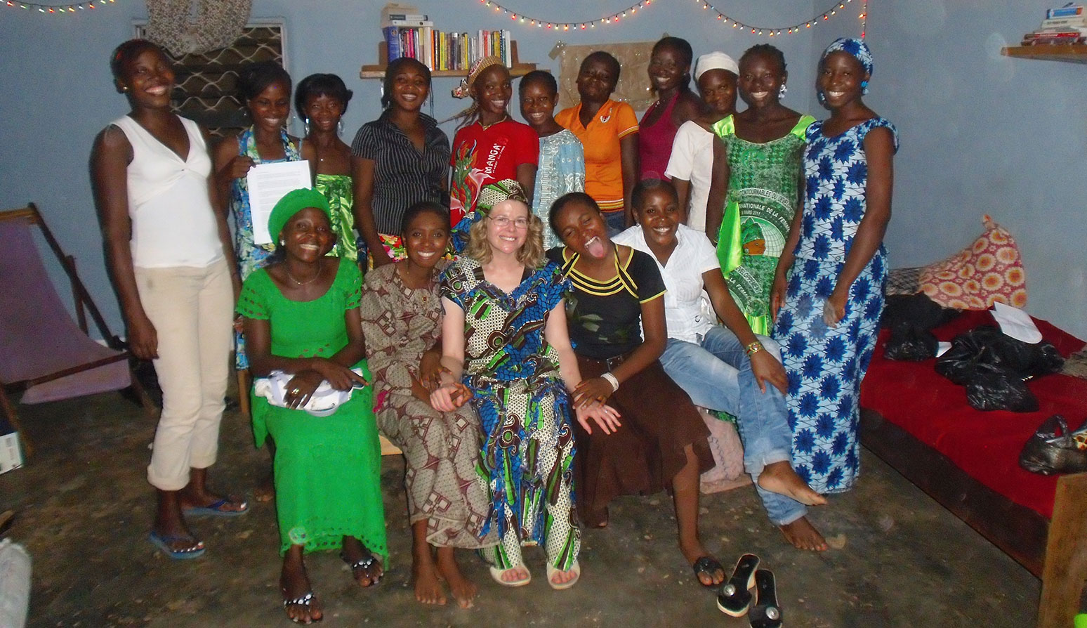 Anne Cheung, center bottom, sits with several scholarship recipients in Meiganga, Cameroon, wearing an outfit they made for her.
