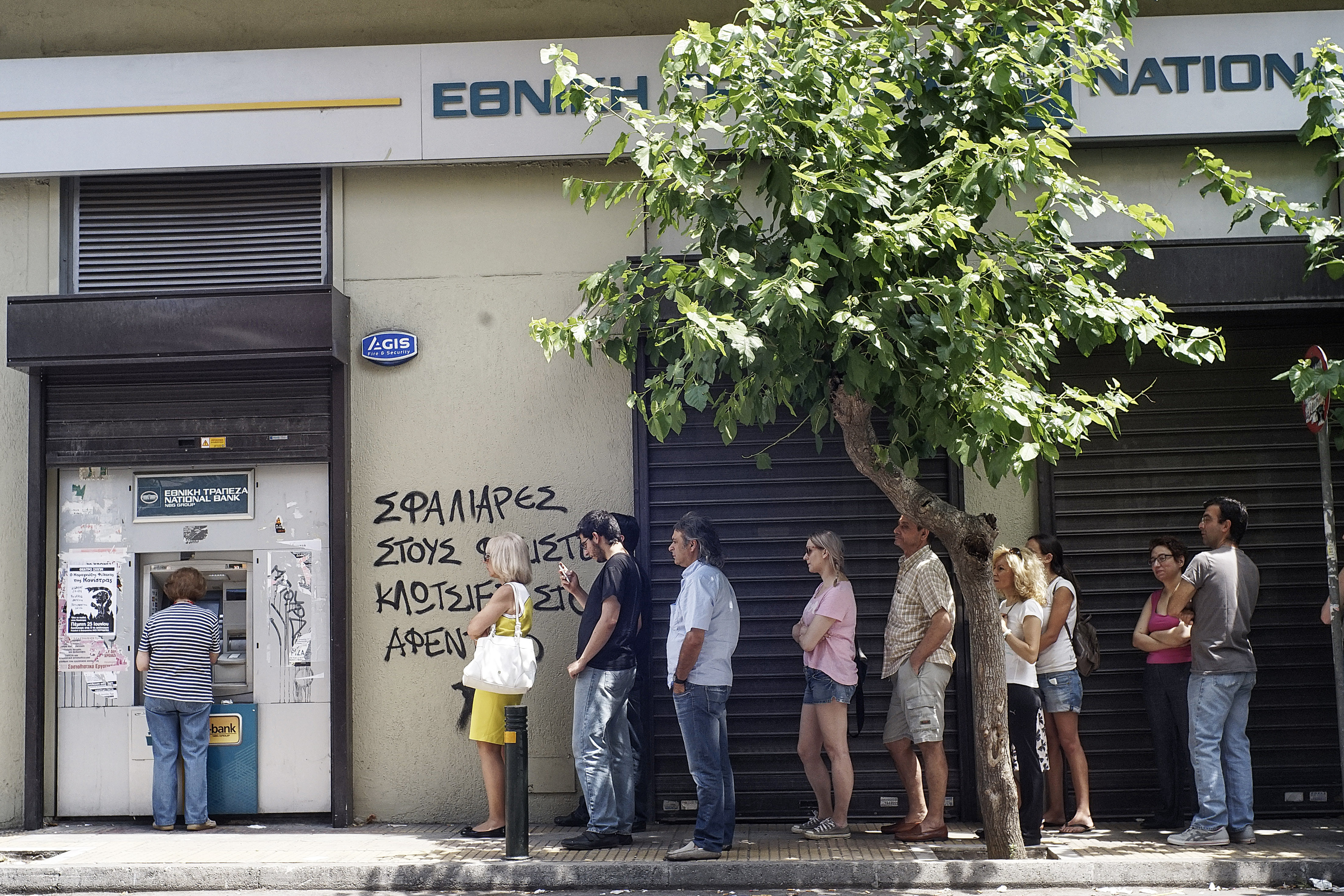 Greeks queue in front of the National Bank to use ATM to withdraw cash as Parliament holds an emergency session for the government's proposed referendum June 27, 2015 in Athens, Greece.