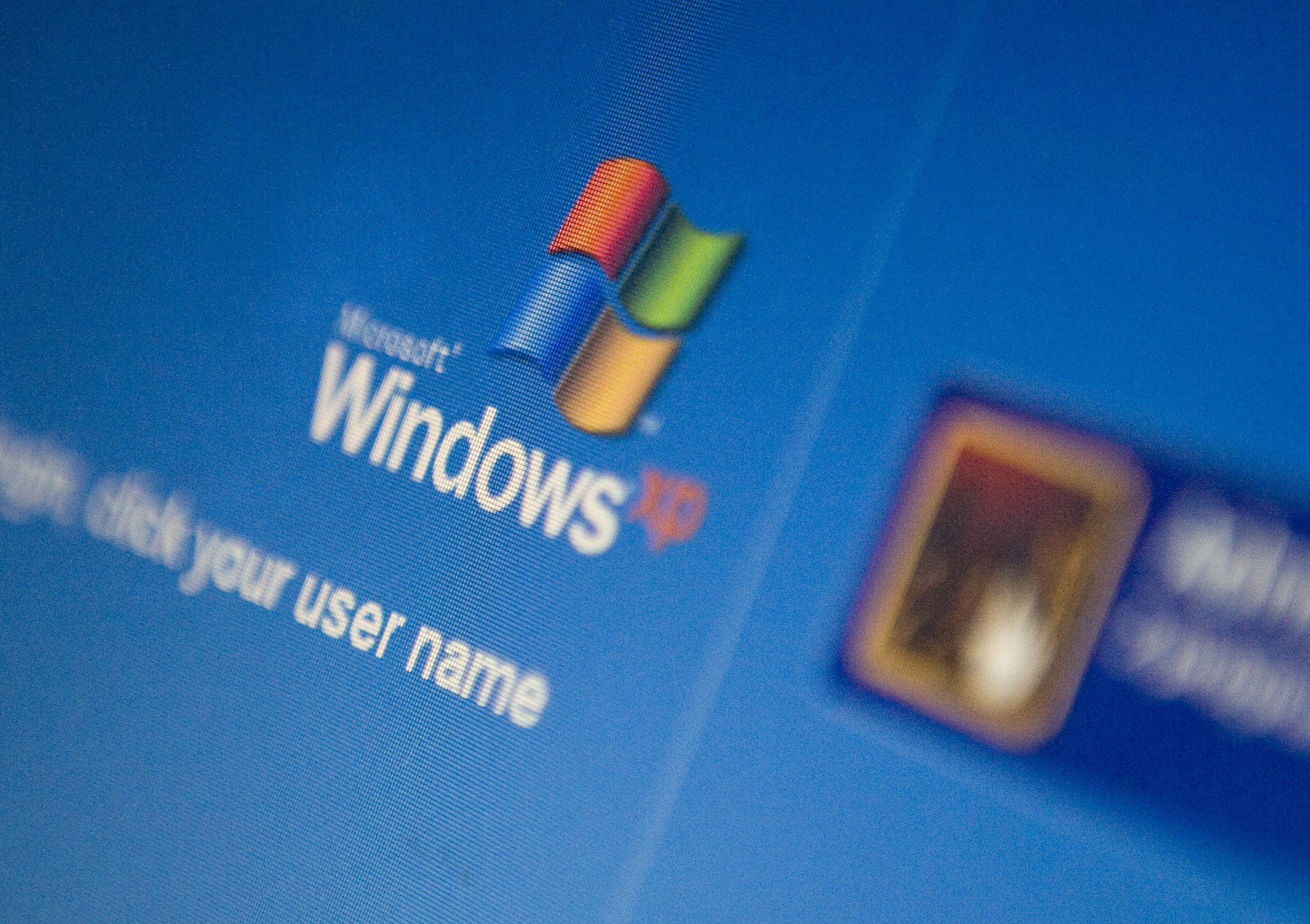 The Microsoft Windows XP log-in screen is displayed on a lap