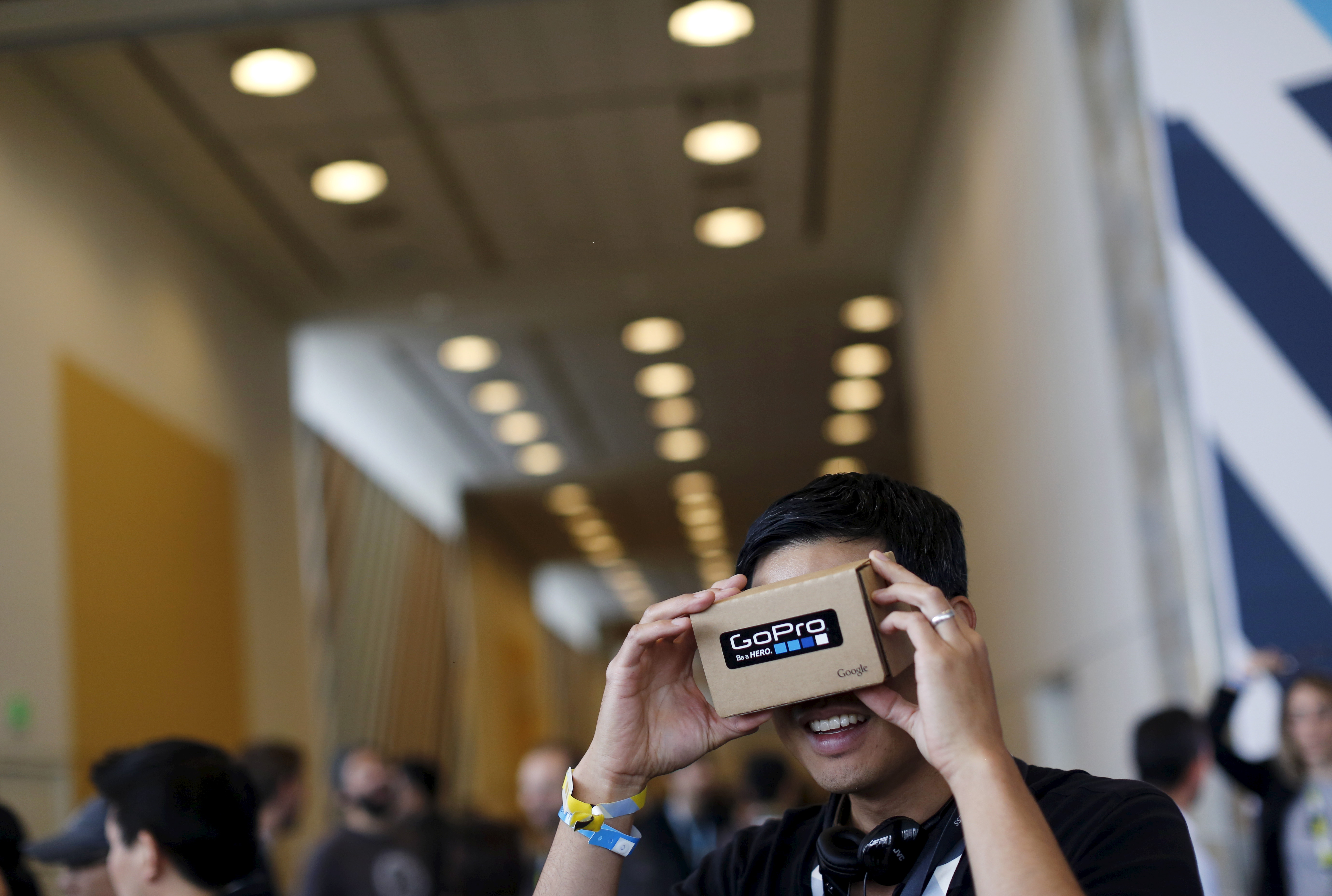 "A conference attendee looks through ""Cardboard,"" a viewer that enables the user to view content from a smart phone in 3D, during the Google I/O developers conference in San Francisco"