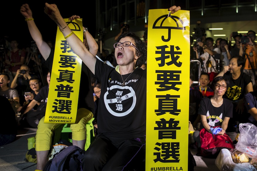 "Pro-democracy protesters shout while holding banners which read ""I want real universal suffrage"" during a demonstration outside Legislative Council in Hong Kong"