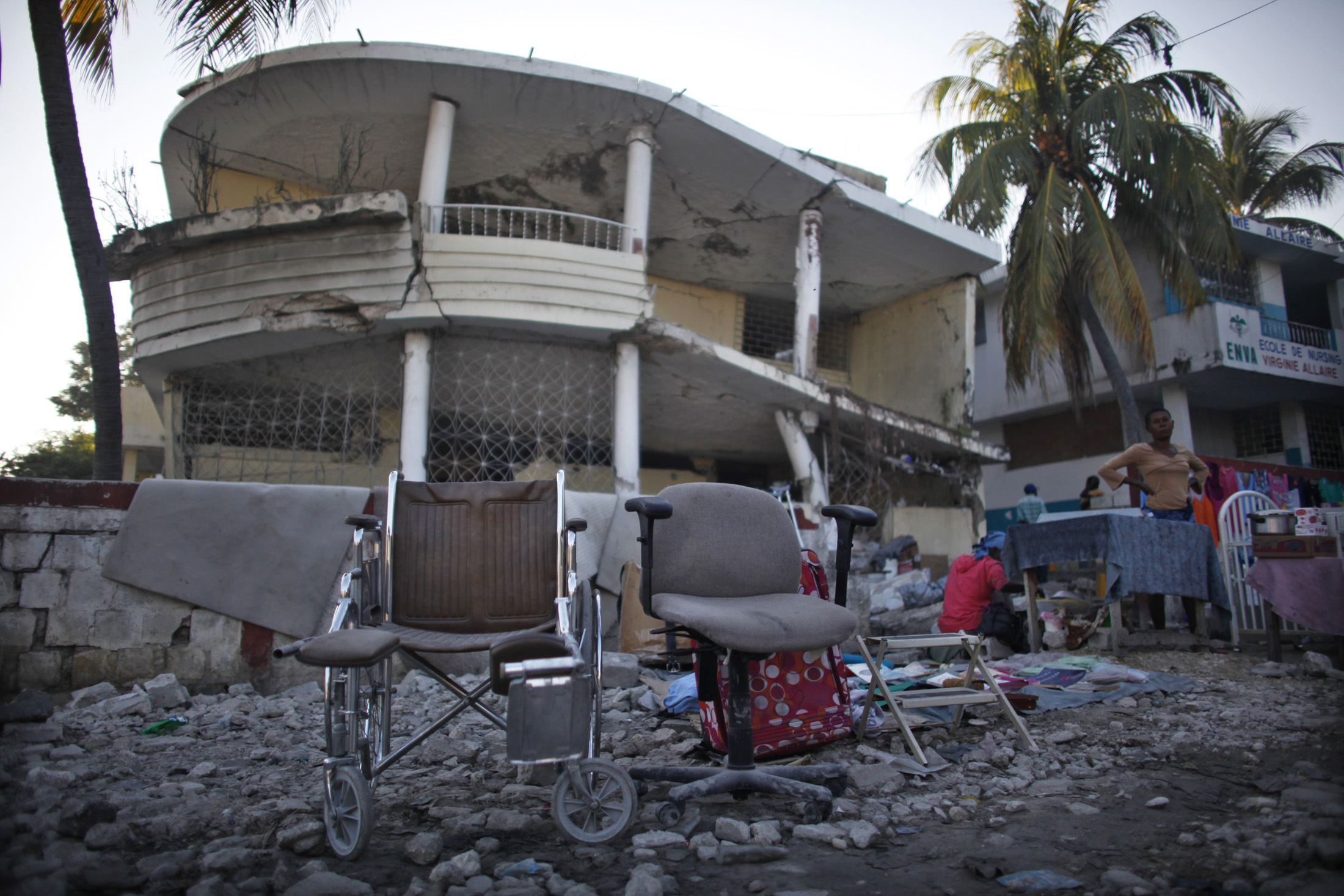 A wheelchair and other items are displayed to sell in front of a destroyed building  by the January 2010 earthquake in Port-au-Prince