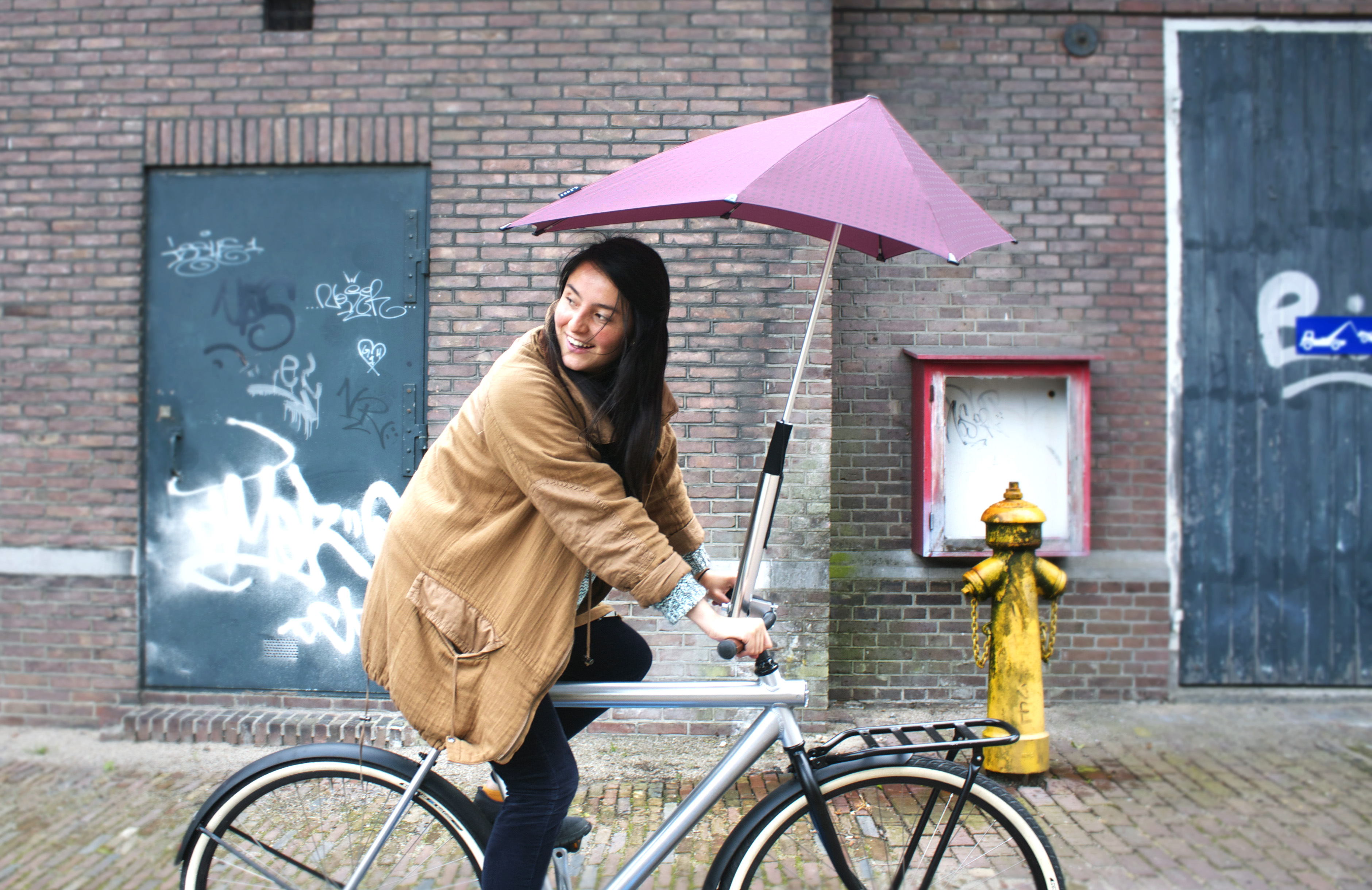 Dutch company Senz's handlebar-mounted umbrella holder keeps bike commuters dry on their way to work.