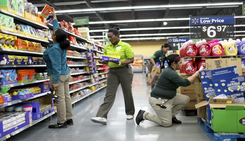 Employees stock shelves at a Miami Walmart. A minimum-wage hike announced in February will bring a raise to some 500,000 workers.